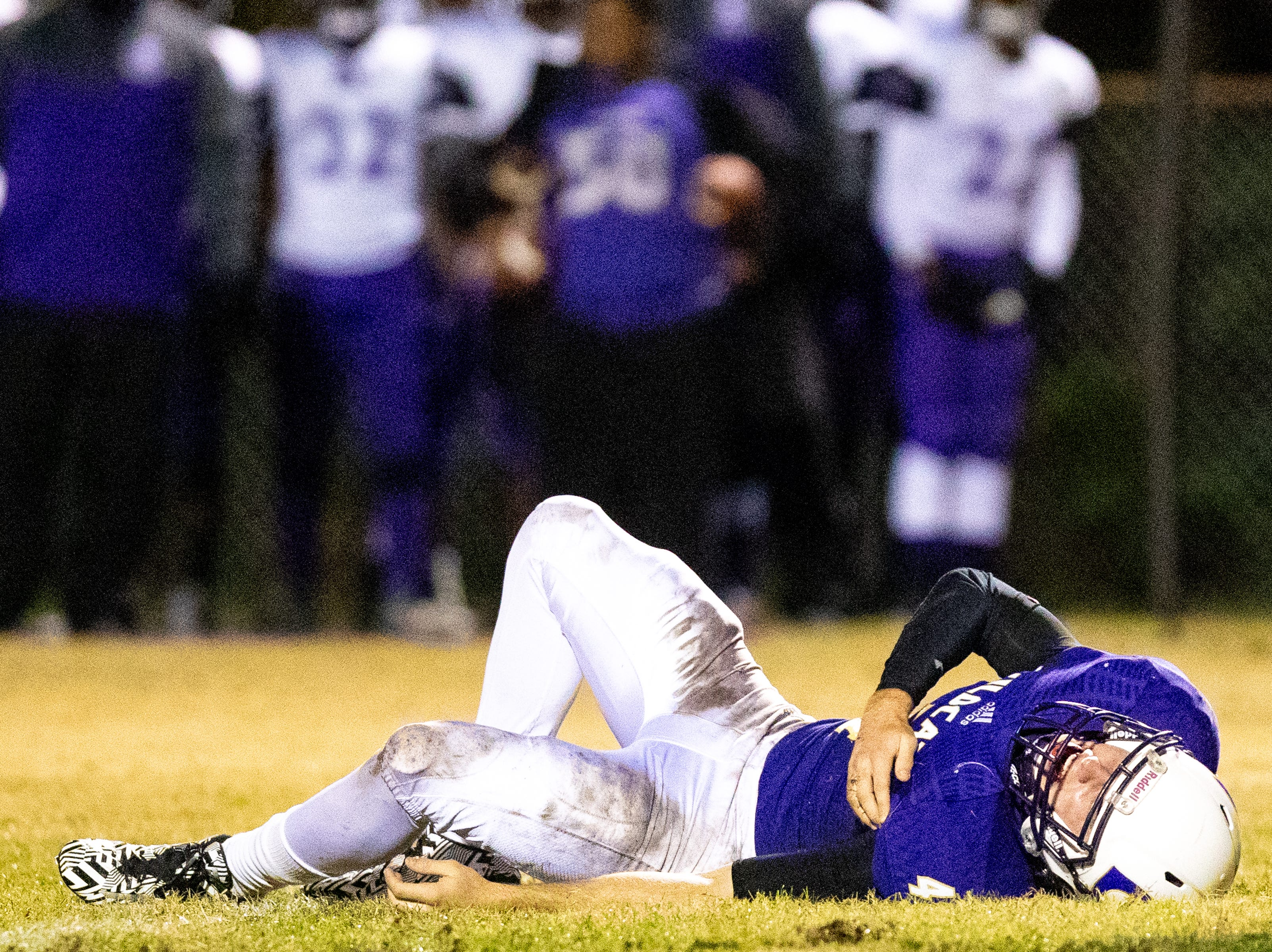 Starting quarterback Ford Cooper (4) of Clarksville High lays on the ground after an injury to his shoulder during the first half at Clarksville High Friday, Nov. 2, 2018, in Clarksville, Tenn.