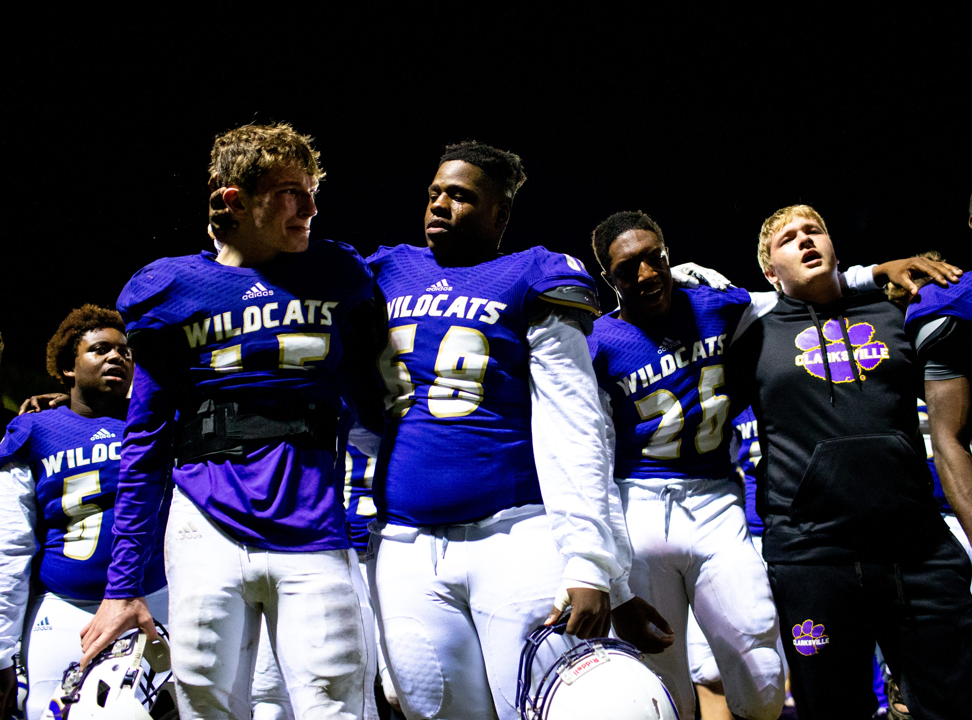 Clarksville High players wrap their arms around each other and sing to the students after losing in overtime at Clarksville High Friday, Nov. 2, 2018, in Clarksville, Tenn.