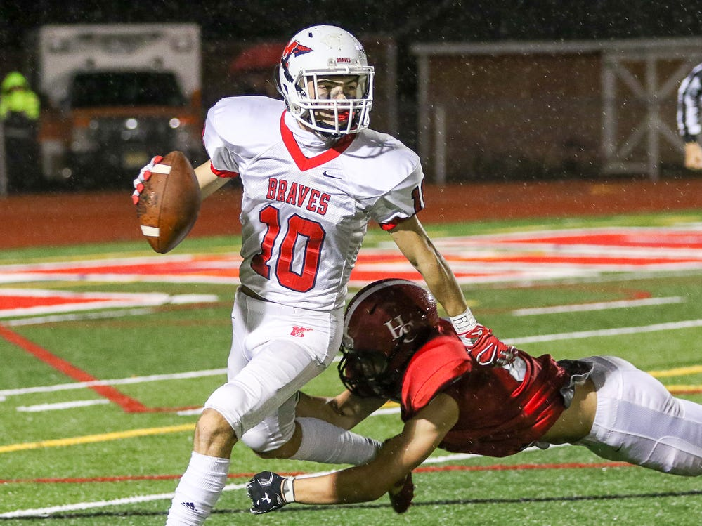 Manalapan's Lucas Demato barely avoids a tackle by Hunterdon Central's Tory Lentine during a Central Group V first round game on Friday, Nov. 2, 2018.