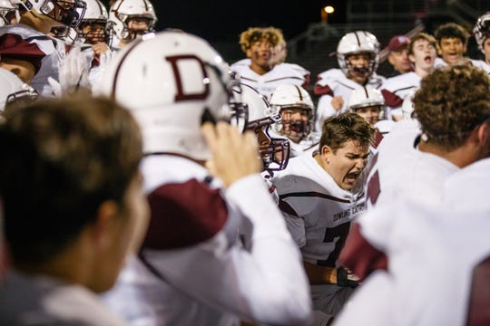 Dowling Catholic's Sean Pattschull (74) cheers with the rest of the Maroon's after the defeated 31-9 to advance to the semi-finals on Friday, Nov. 2, 2018, in West Des Moines.
