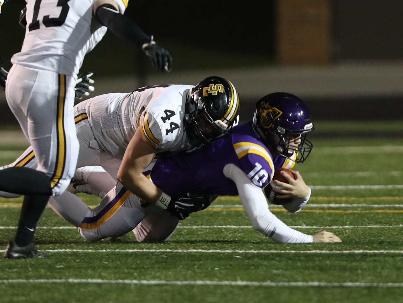 Nov 2, 2018; Johnston, IA, USA; Johnston Dragons Andrew Nord (10) is tackled by Southeast Polk Rams Tanner VanElsen (44) at Johnston Stadium. The Rams beat the Dragons 21-7.