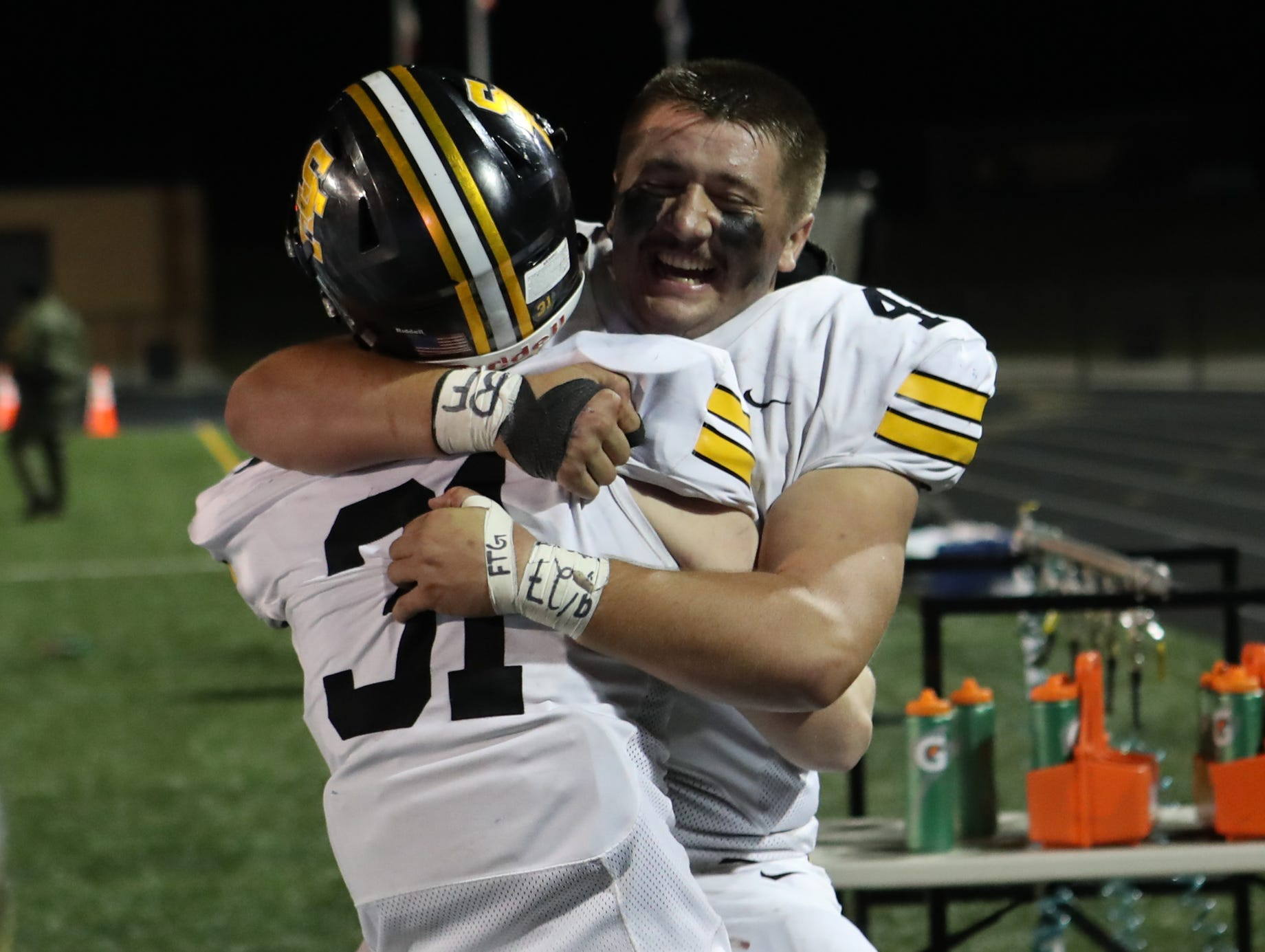 Nov 2, 2018; Johnston, IA, USA;  Southeast Polk Rams Bo Ira (48) and Southeast Polk Rams Carter Olesen (31) celebrate their win over the Johnston Dragons at Johnston Stadium. The Rams beat the Dragons 21-7.