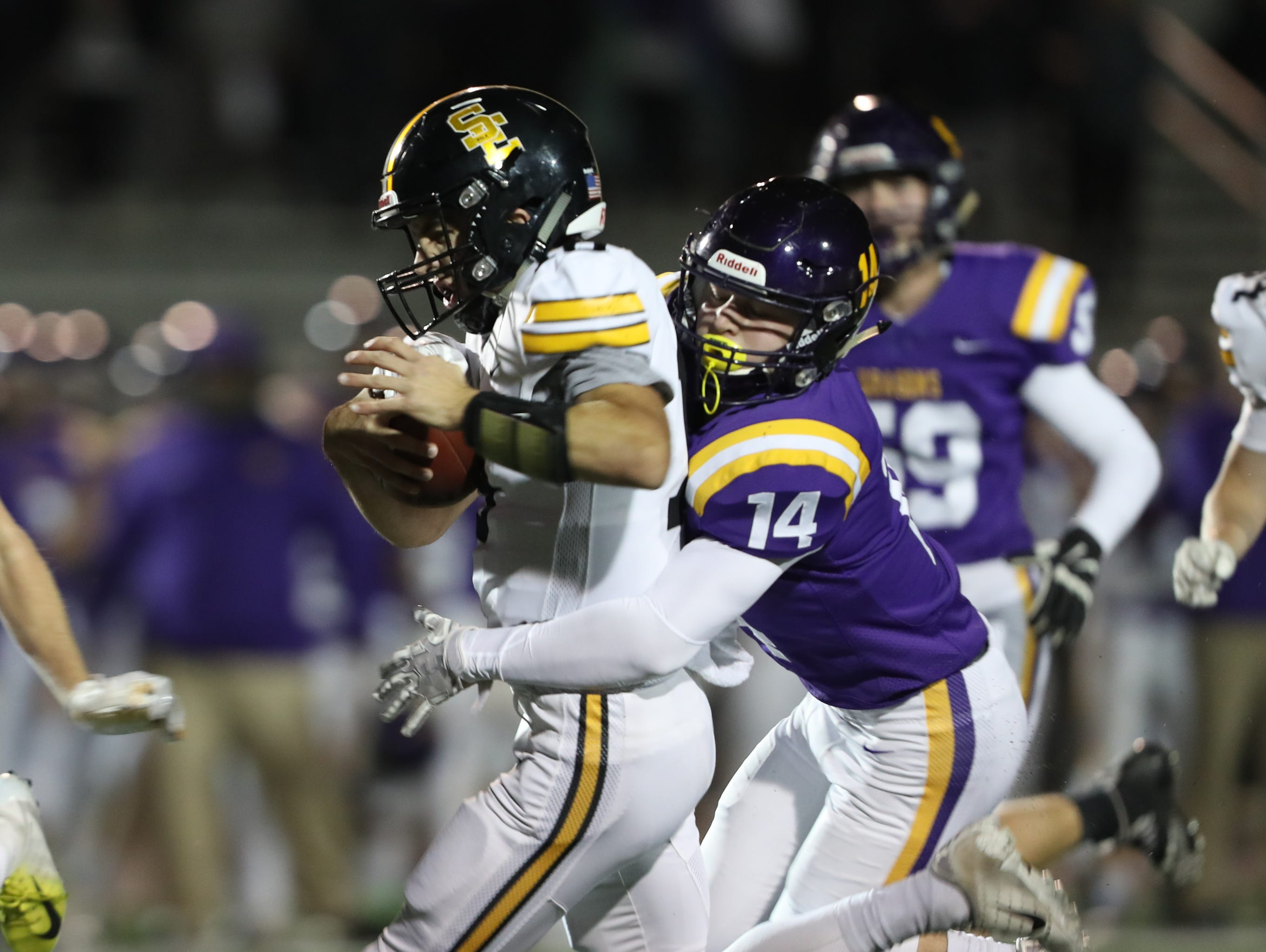 Nov 2, 2018; Johnston, IA, USA; Johnston Dragons Cal Killian (14) tackles Southeast Polk Rams Josiah Cole (18) at Johnston Stadium. The Rams beat the Dragons 21-7.