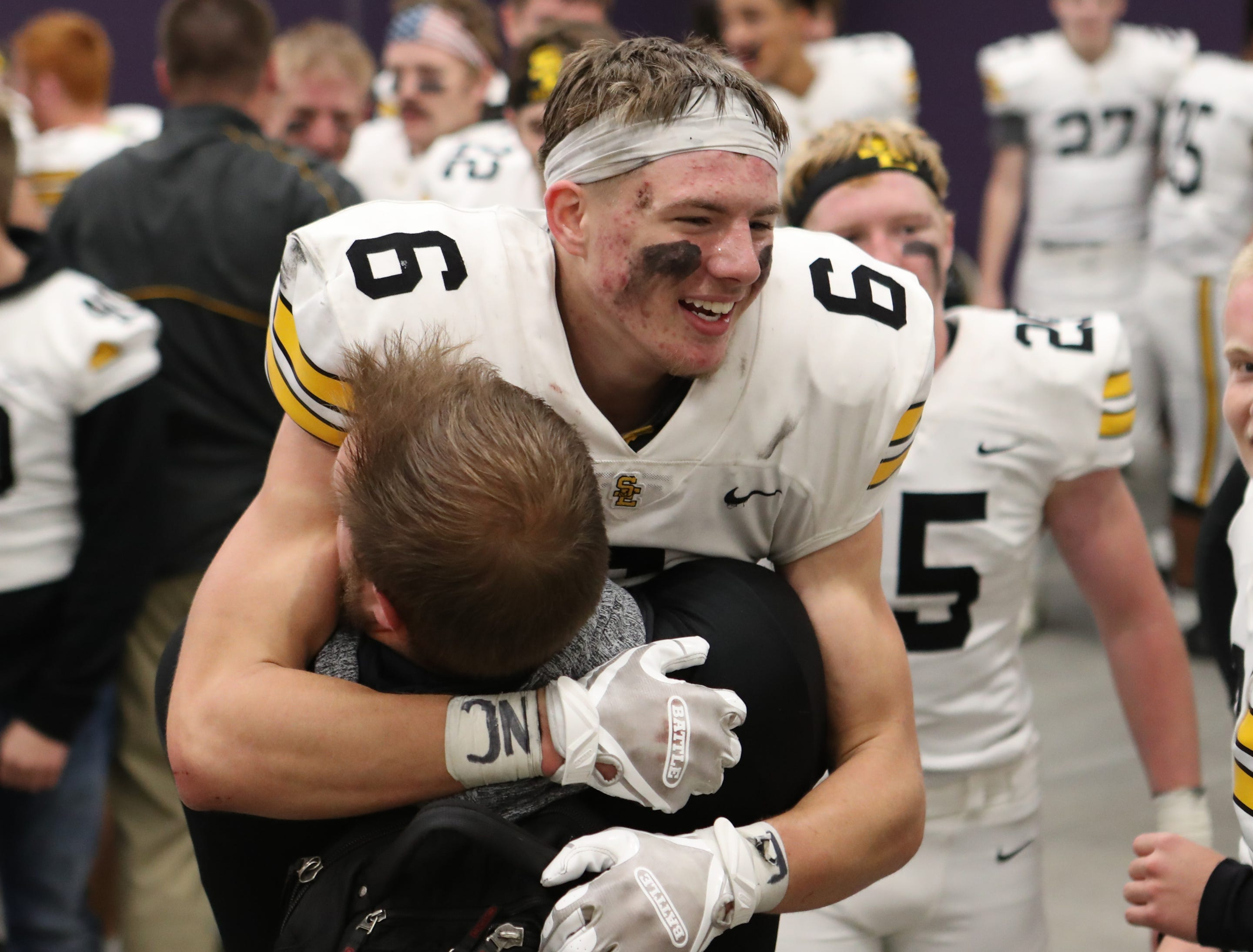 Nov 2, 2018; Johnston, IA, USA; Southeast Polk Rams Dylan Travis (6) hugs Coach Soelter after their win at Johnston Stadium. The Rams beat the Dragons 21-7.