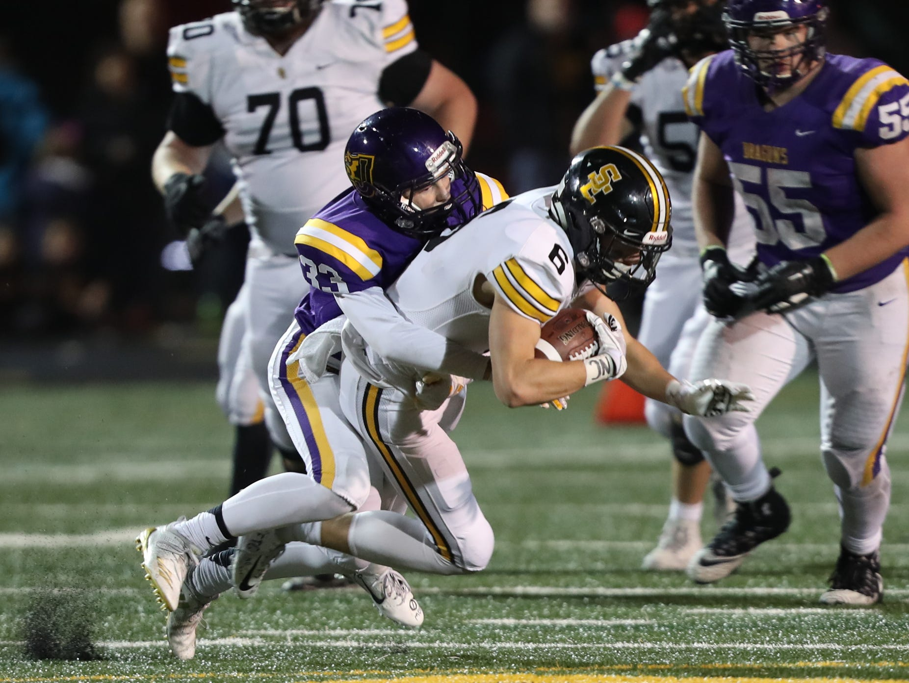 Nov 2, 2018; Johnston, IA, USA; Southeast Polk Rams Dylan Travis (6) is tackled by Johnston Dragons Caleb Helgeson (33) at Johnston Stadium. The Rams beat the Dragons 21-7.