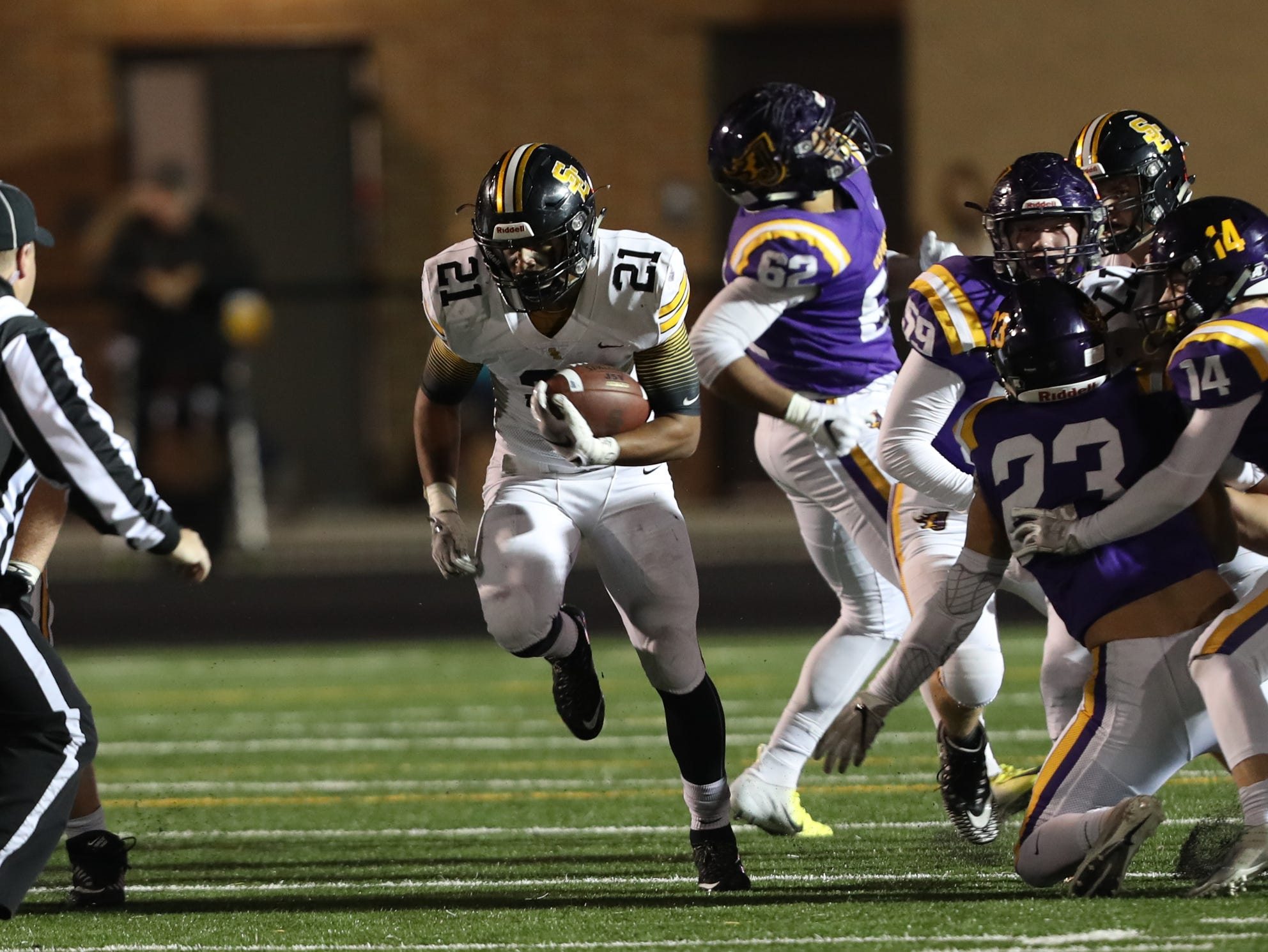 Nov 2, 2018; Johnston, IA, USA; Southeast Polk Rams Gavin Williams (21) runs for a first down against the Southeast Polk Rams at Johnston Stadium. The Rams beat the Dragons 21-7.