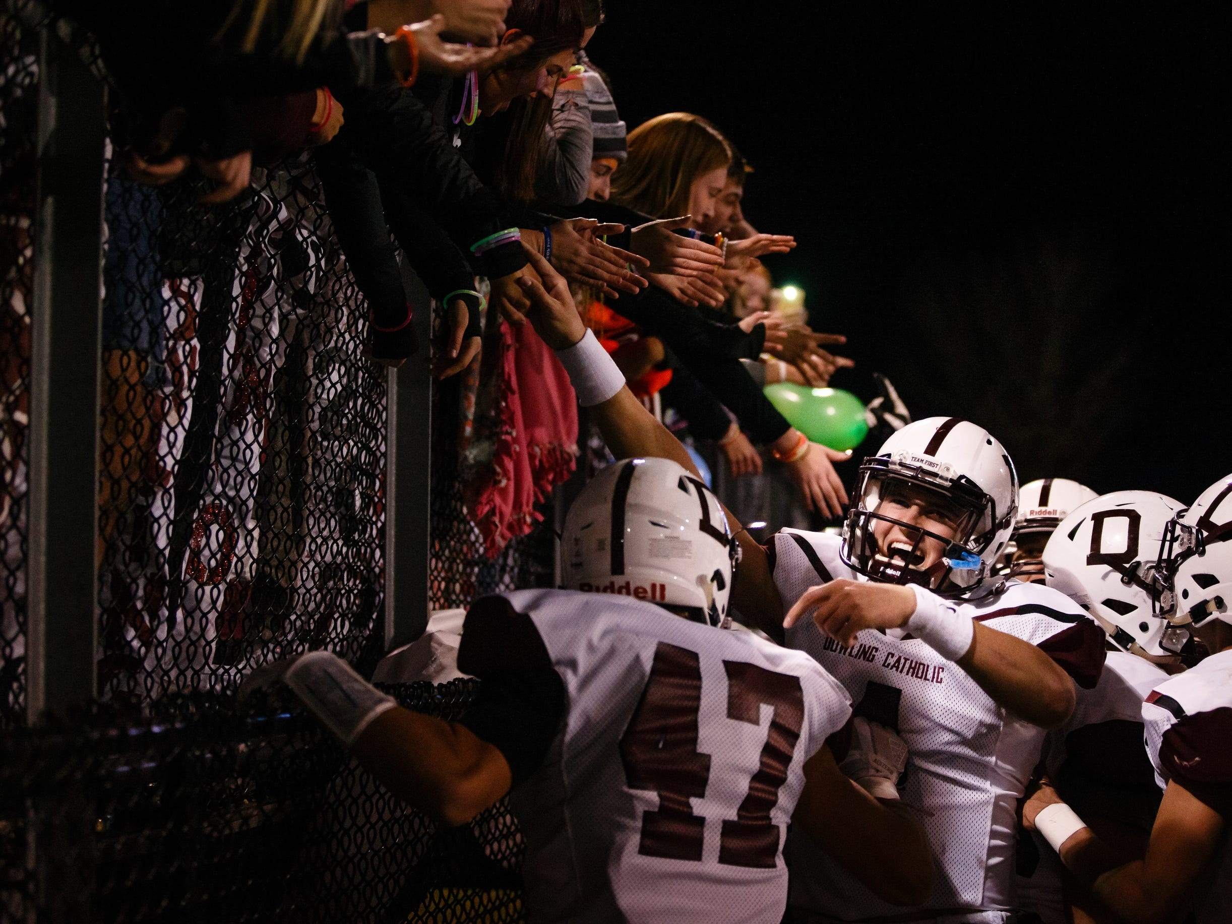 Dowling Catholic players celebrate with their fan section after defeating Valley 31-9 to advance to the semi-finals on Friday, Nov. 2, 2018, in West Des Moines.
