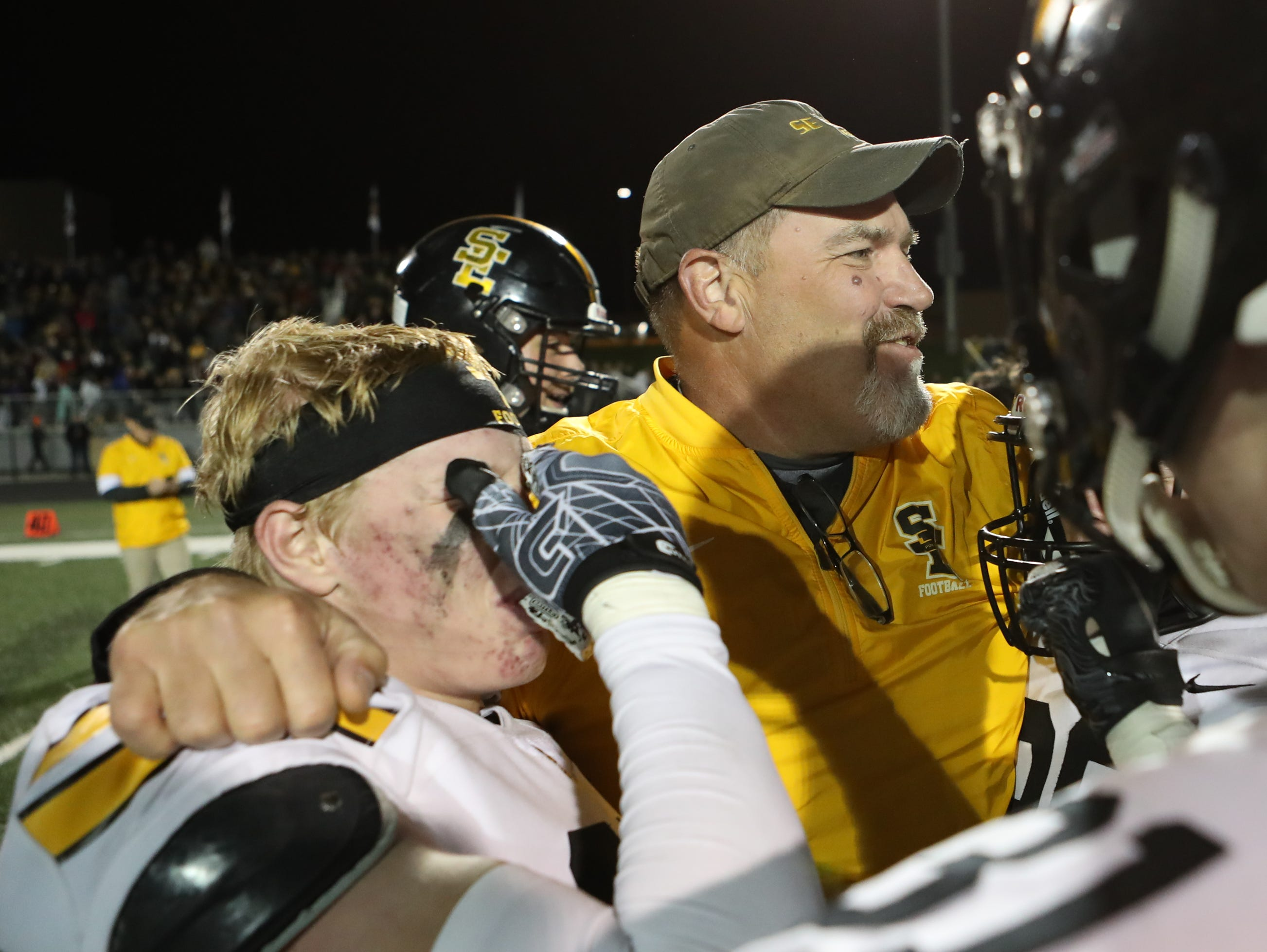 Nov 2, 2018; Johnston, IA, USA; Southeast Polk Rams Zach Strickland (25) and Southeast Polk Rams defensive coordinator Don Starcevich celebrate at Johnston Stadium. The Rams beat the Dragons 21-7.