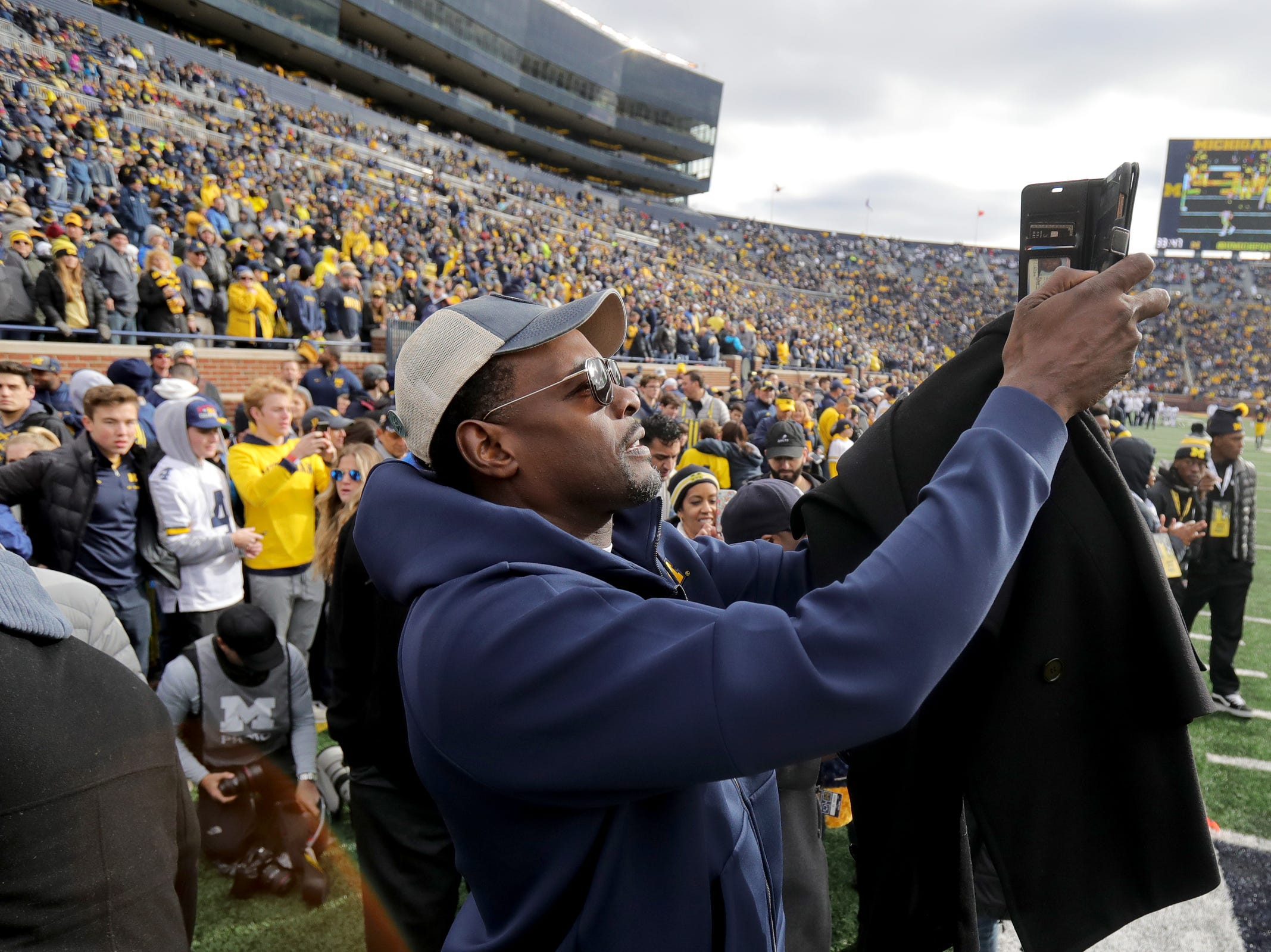 Former Michigan basketball player Chris Webber takes a selfie on the football field prior to the start of the Michigan and Penn State game on Saturday, Nov. 3,2018, at Michigan Stadium.
