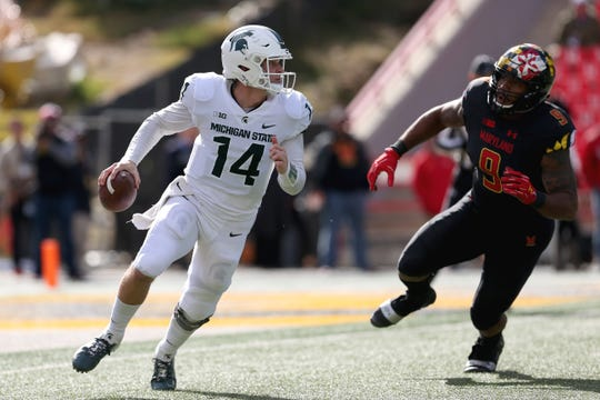 Michigan State QB Brian Lewerke runs past Maryland's Byron Cowart during the first half at Capital One Field on Saturday, Nov. 3, 2018 in College Park, Maryland.