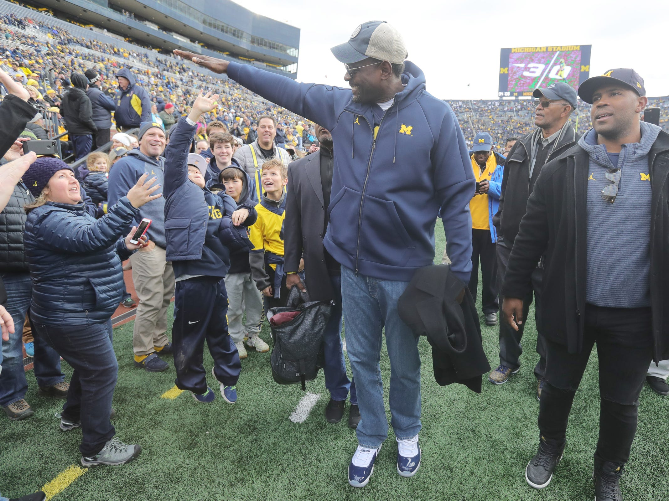 Former Michigan basketball player Chris Webber gives out high fives with fans on the football field prior to the start of the Michigan and Penn State game on Saturday, Nov. 3,2018, at Michigan Stadium.