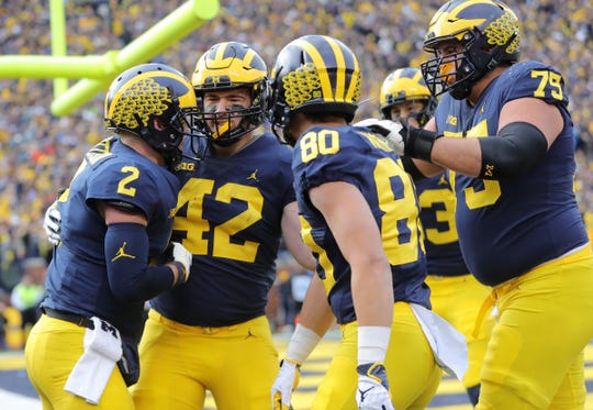Shea Patterson (2) celebrates his TD with Ben Mason, Oliver Martin and Greg Robinson against Penn State during the first half Saturday in Ann Arbor.