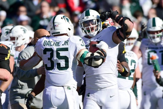 Joe Bachie celebrates with Kenny Willekes after recovering a fumble against Maryland on Nov. 3, 2018.