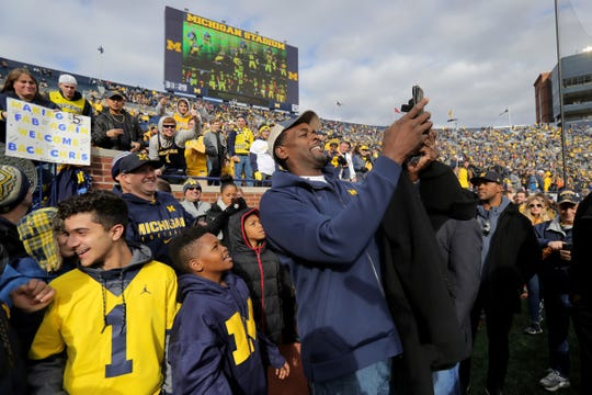 Former Michigan basketball player Chris Webber takes a selfie with fans on the football field prior to the start of the Michigan and Penn State game on Saturday, Nov. 3,2018, at Michigan Stadium.