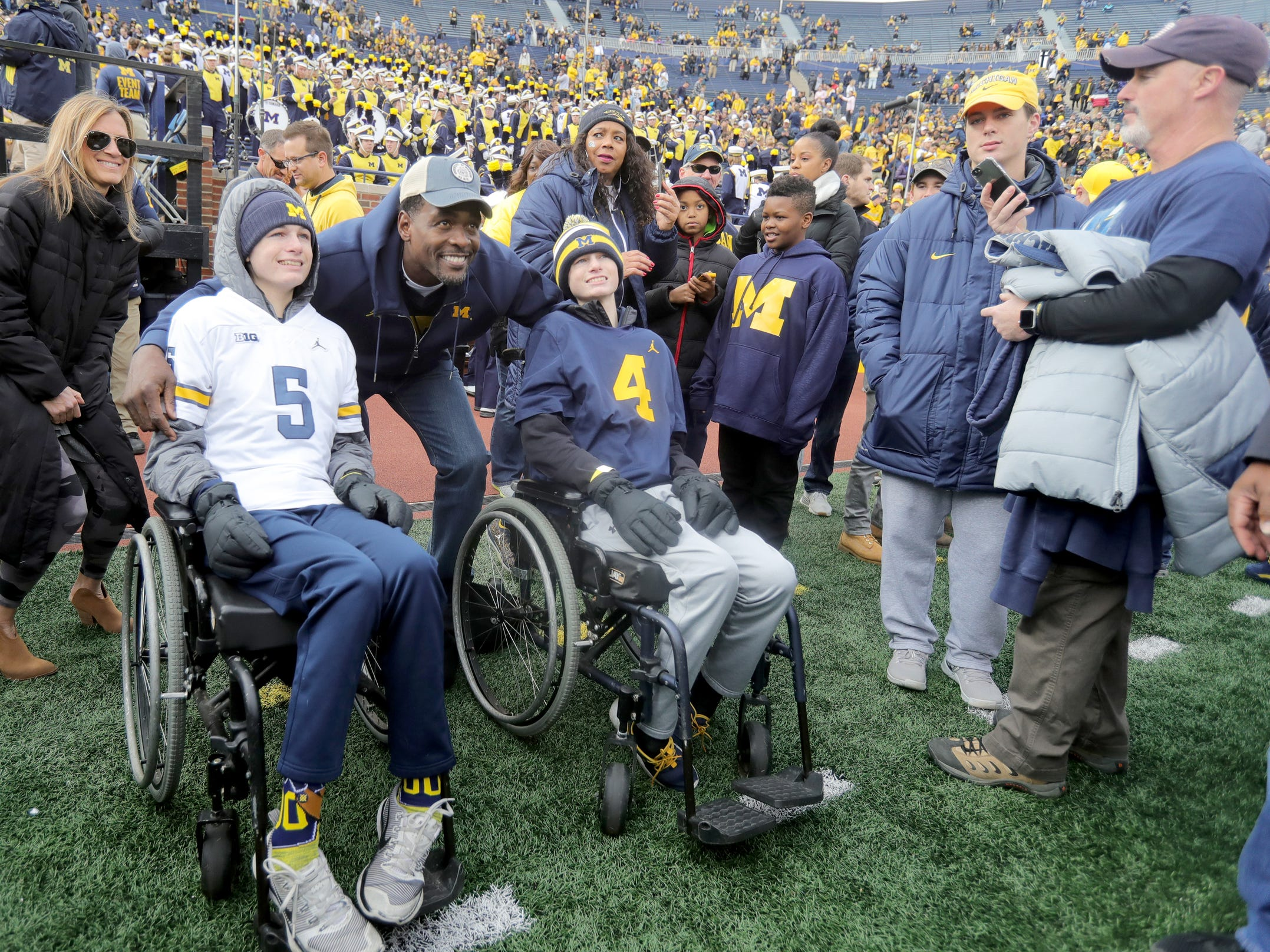 Former Michigan basketball player Chris Webber gets his picture taken with fans on the field prior to the start of the Penn State game, November 3, 2018 at Michigan Stadium in Ann Arbor.