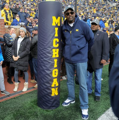 Former Michigan basketball player Chris Webber poses for a picture by the goal post on the football field prior to the start of the Michigan and Penn State game on Saturday, Nov. 3,2018, at Michigan Stadium.