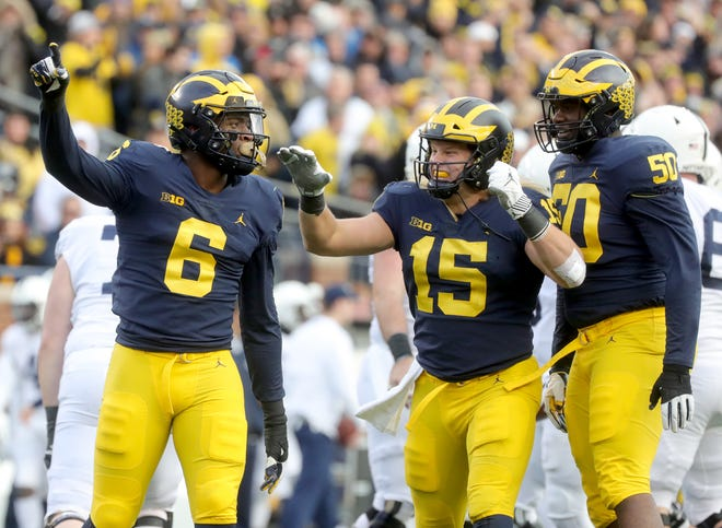 Michigan's Chase Winovich, center, celebrates his sack against Penn State with teammates Josh Uche, left, and Michael Dwumfour during the first half Saturday, November 3, 2018 at Michigan Stadium in Ann Arbor.