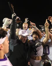Warren De La Salle head coach Mike Giannone and his team raise the district championship trophy after the 35-7 win over Oak Park on Friday, November 2, 2018 at Oak Park High School in Oak Park, Mich.