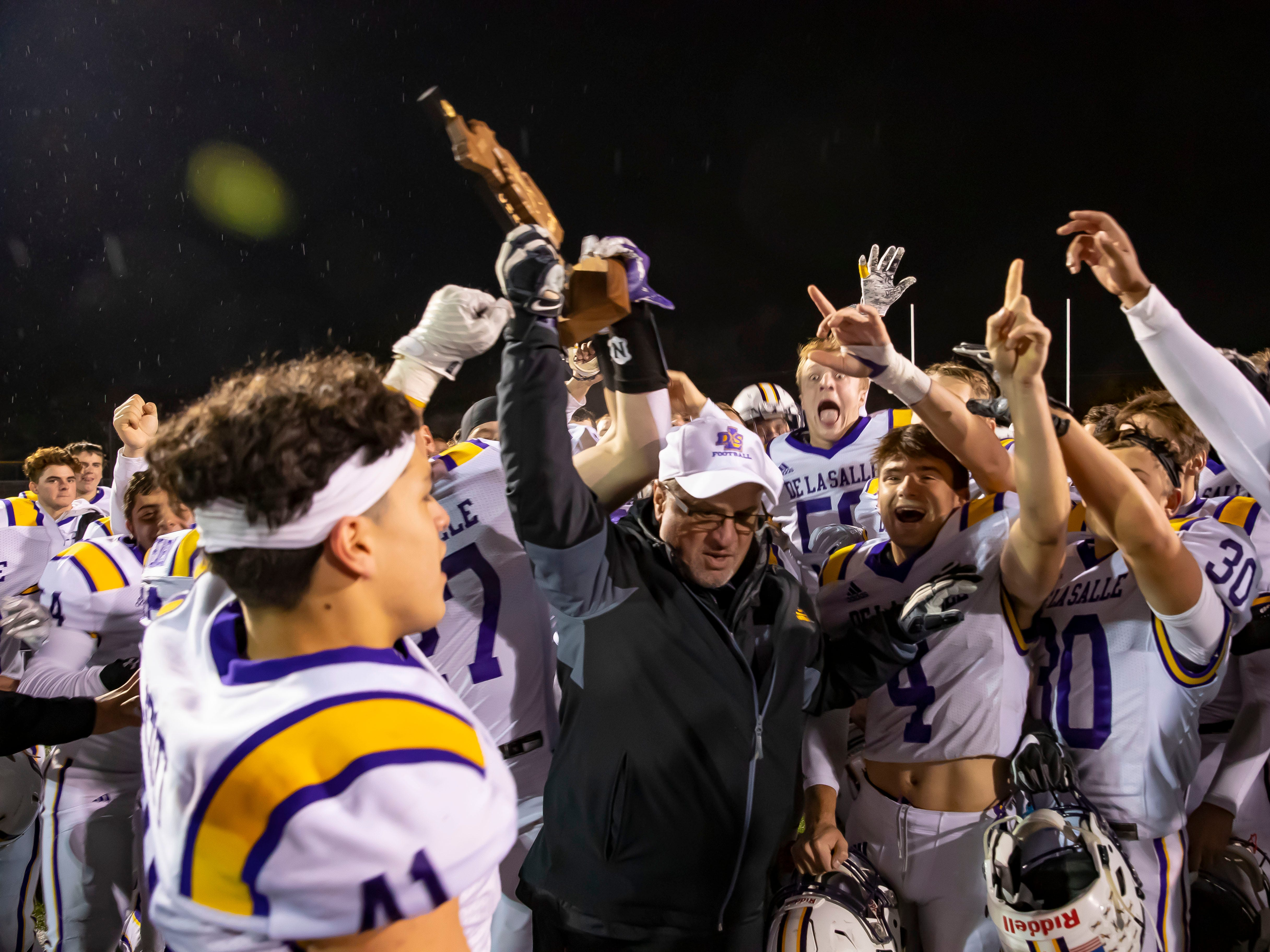 Warren De La Salle head coach Mike Giannone holds up the championship trophy in front of his team after they defeated Oak Park 35-7.