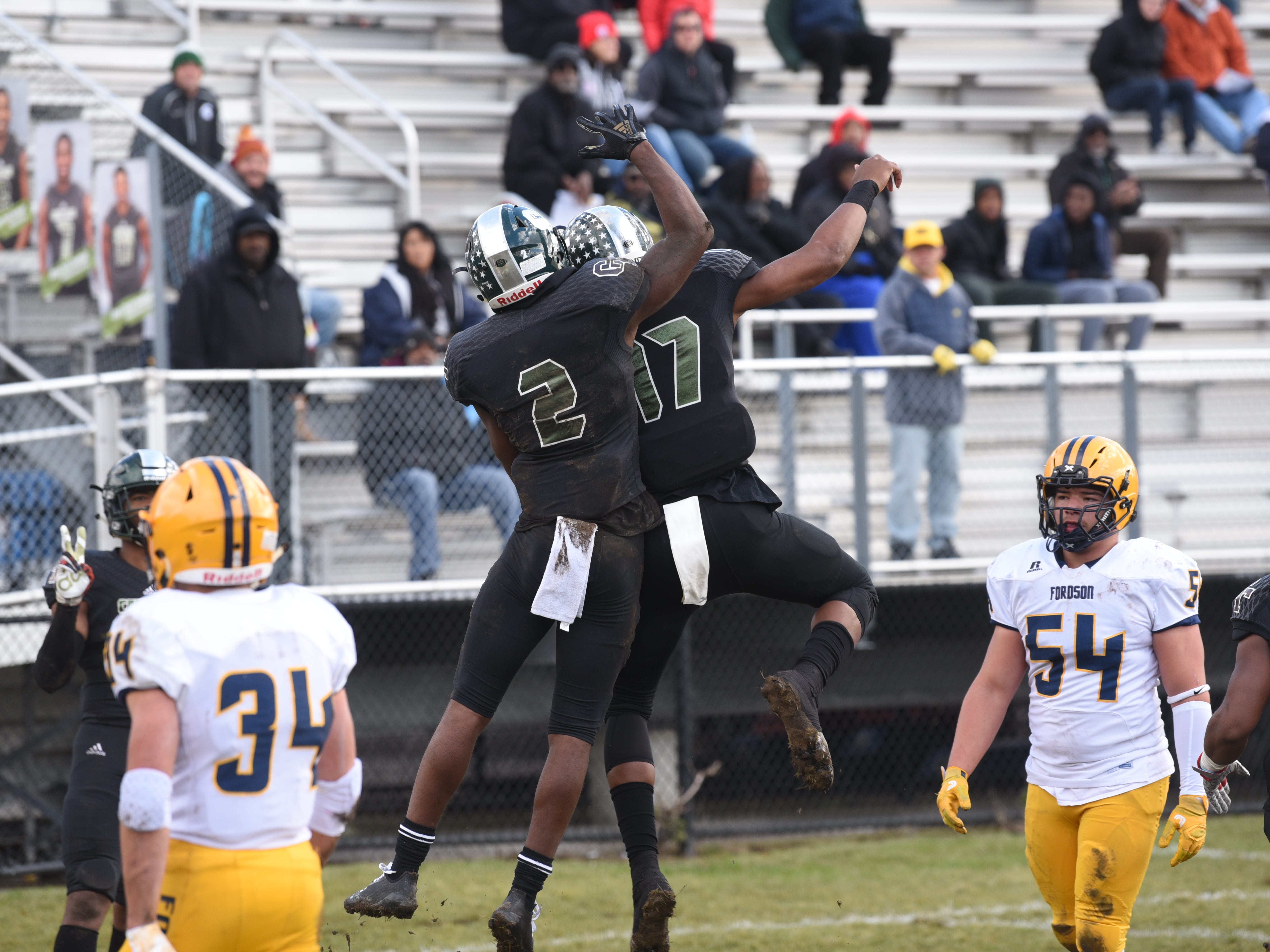 Cass Technical High School players Kyron McKinnie-Harper (2) and Jalen Graham (17) celebrate a first-quarter touchdown against Dearborn Fordson High School