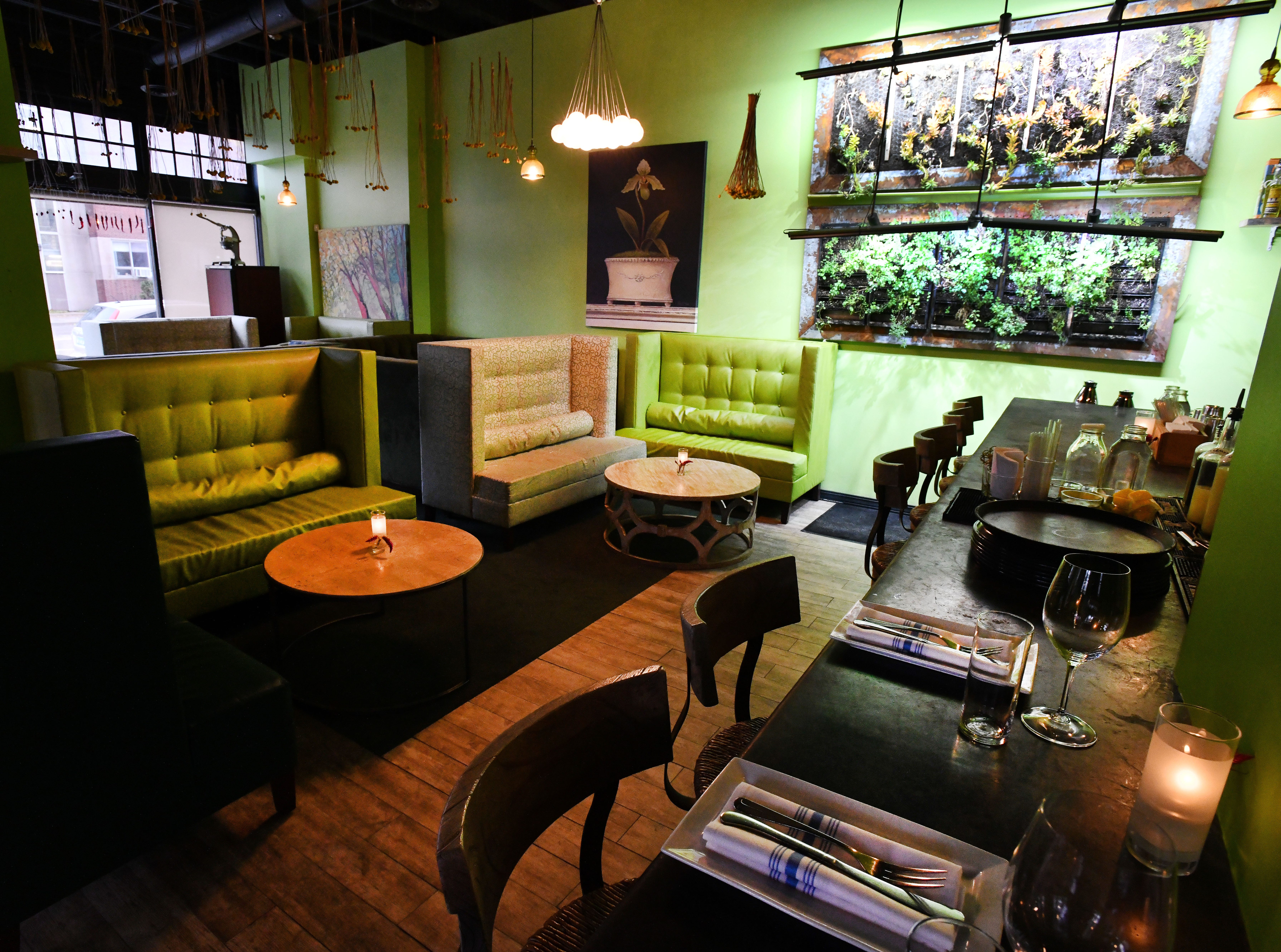 A seating area along side the bar with a wall garden.