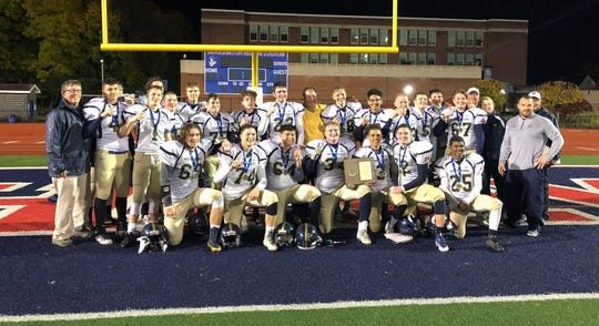 Elmira Notre Dame players pose with their plaque after a 38-20 win over Lansing in the Section 4 eight-man football championship game Nov. 2, 2018 at Binghamton Alumni Stadium.
