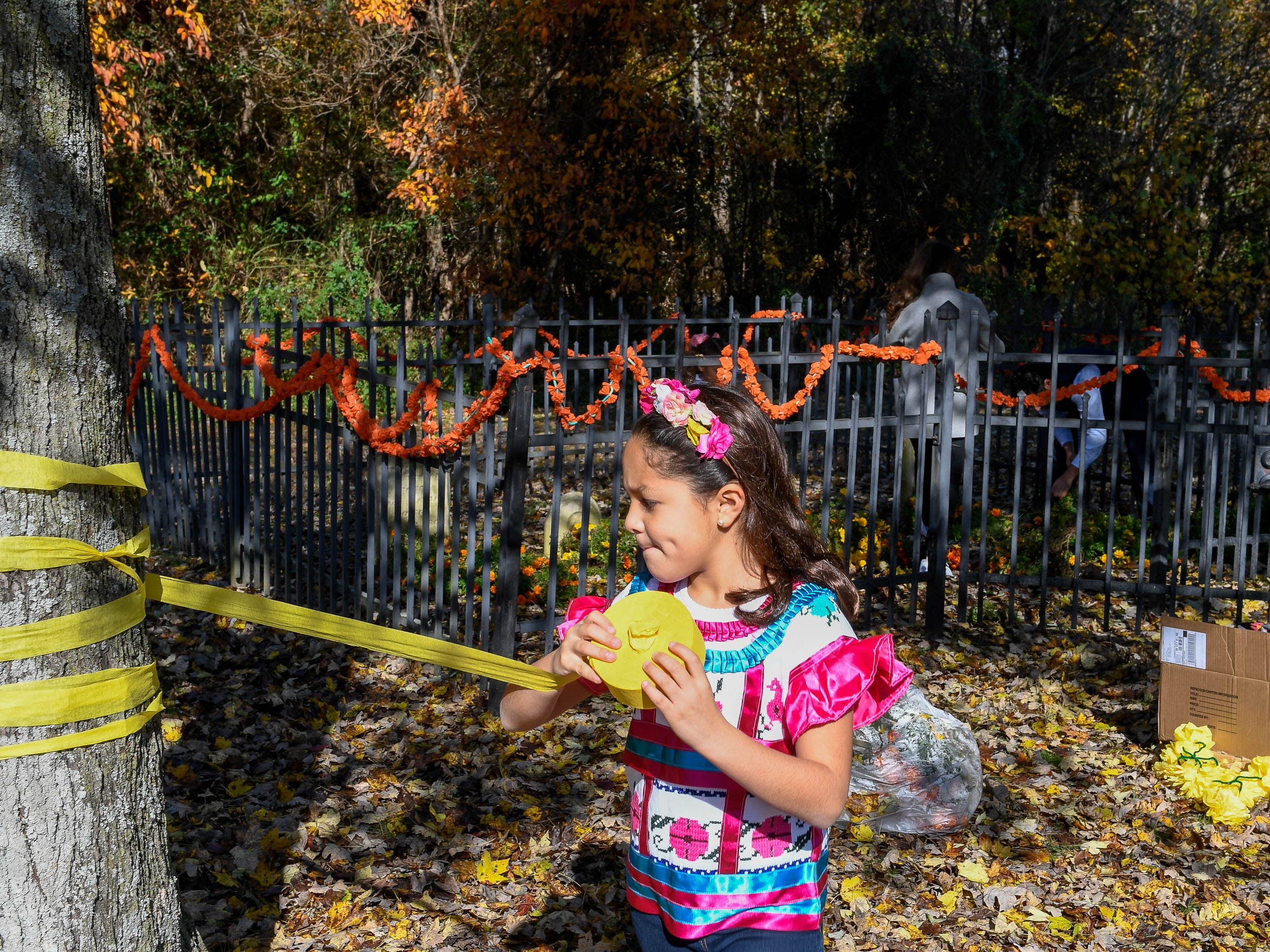 Berenice Gonzalez, eight years-old, wraps yellow ribbon around the Angel family cemetery at the Day of the Dead held at Evansville's Angel Mounds State Historic Site Saturday, November 3, 2108.