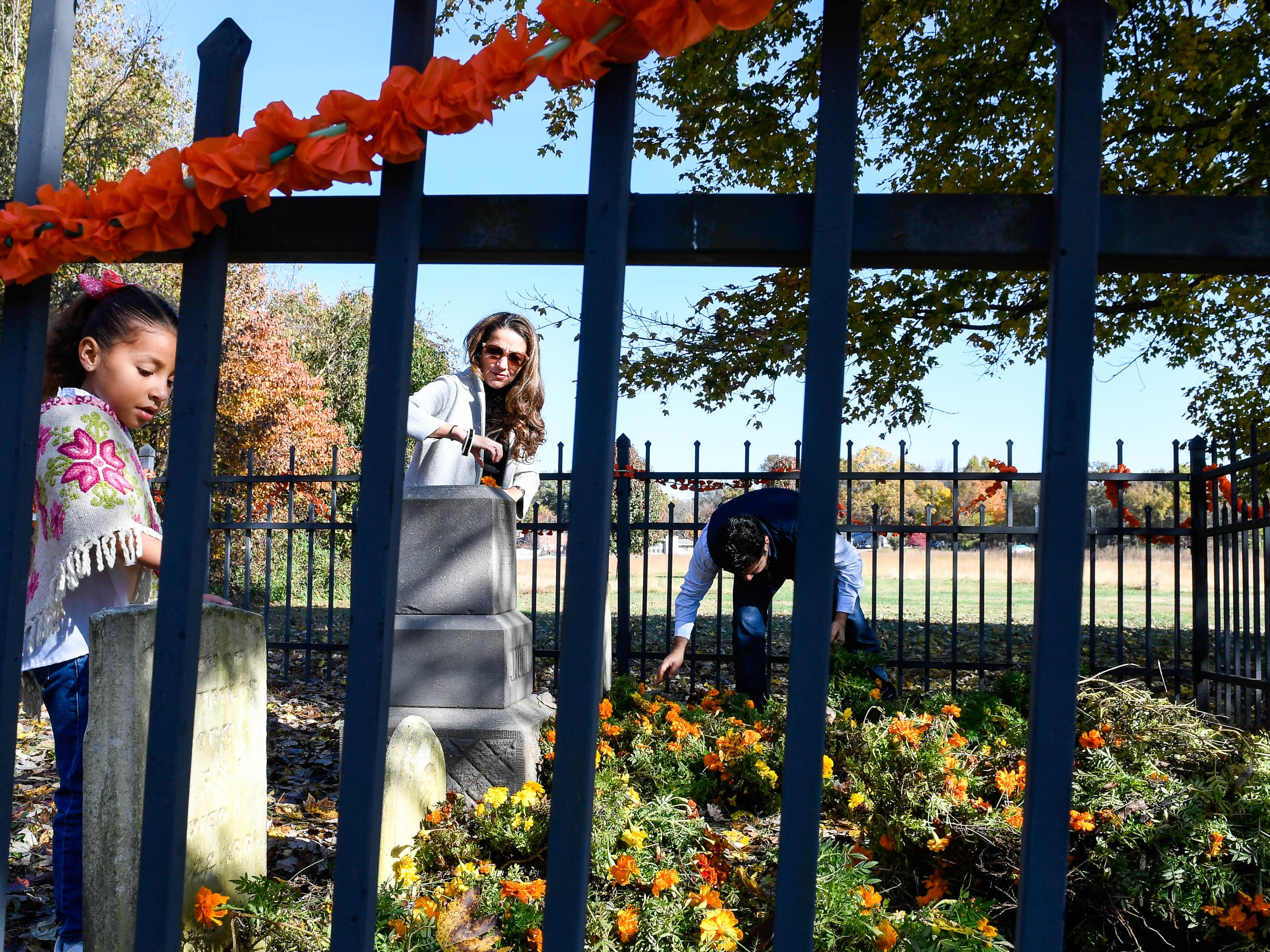 Jimena, six years-old, Berenice and Gerardo Gonzalez decorate the Angel family graves for the Day of the Dead held at Evansville's Angel Mounds State Historic Site Saturday, November 3, 2108.