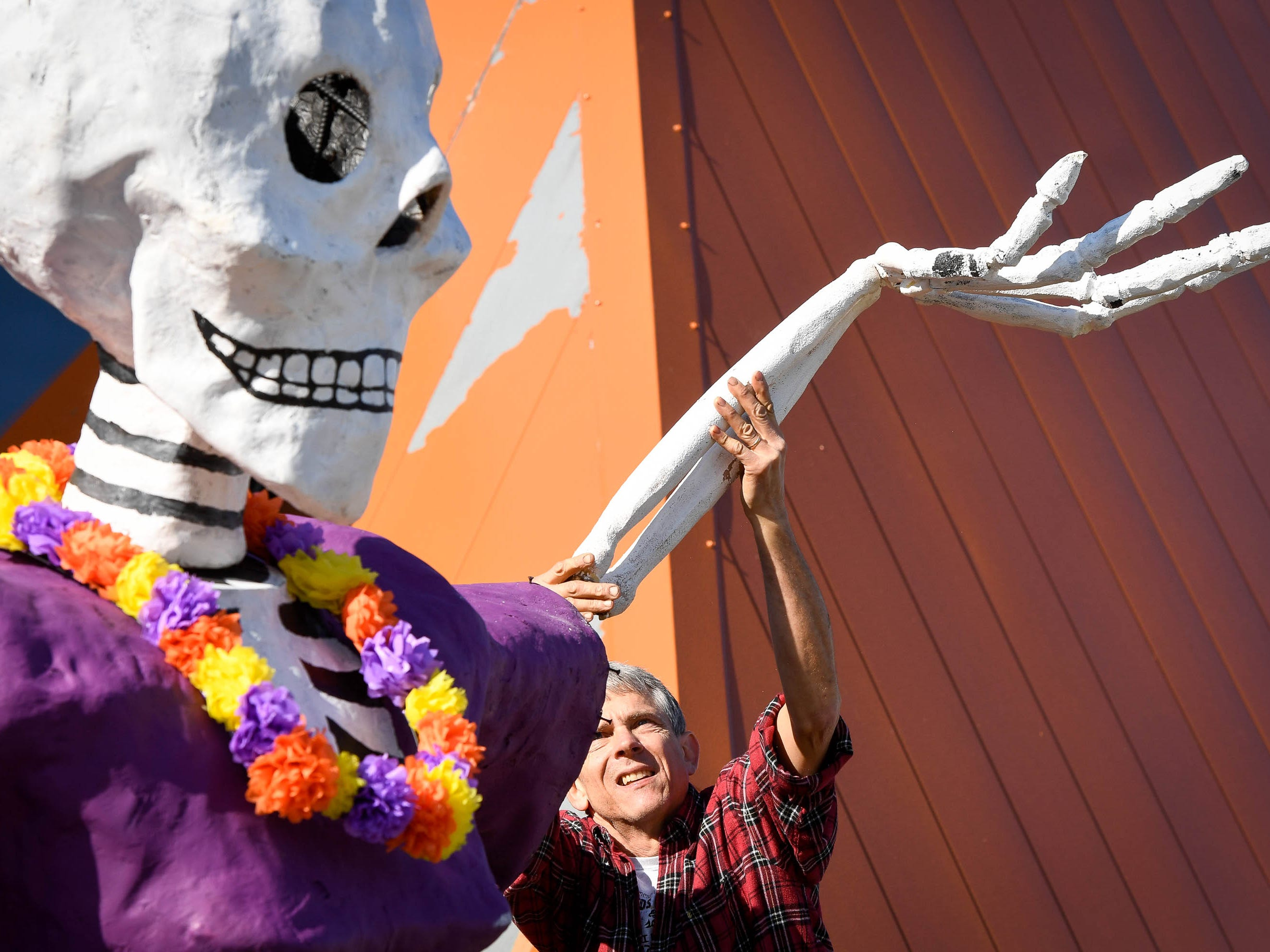 Eric Ridenourr with Montessori Academy attaches one of the arms to the folk caricature La Catrina guarding the door to the museum  at the Day of the Dead held at Evansville's Angel Mounds State Historic Site Saturday, November 3, 2108.