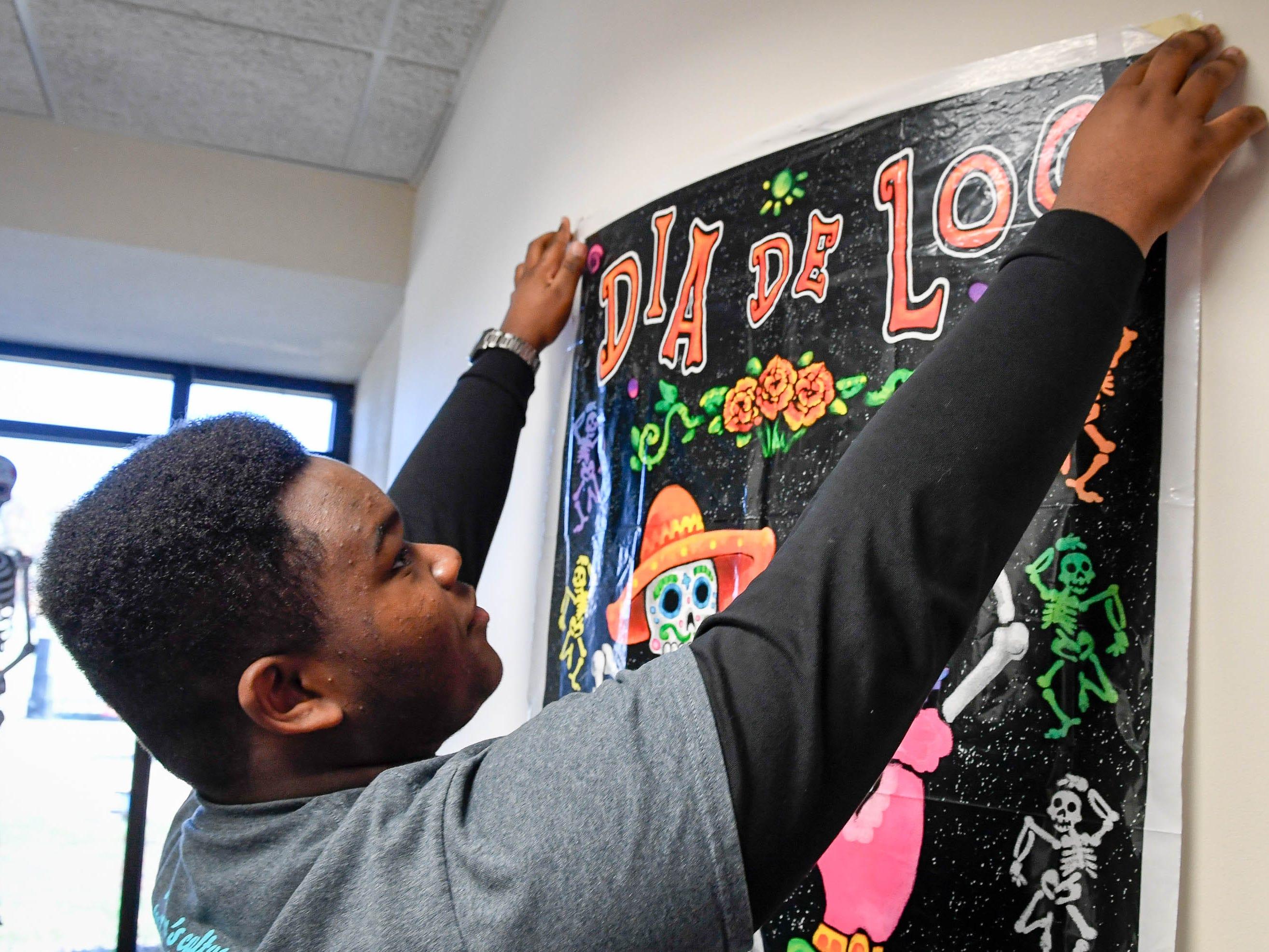 Bosse High School student Andre HIcks hangs a poster in the Angel Mounds museum at the Day of the Dead held at Evansville's Angel Mounds State Historic Site Saturday, November 3, 2108.