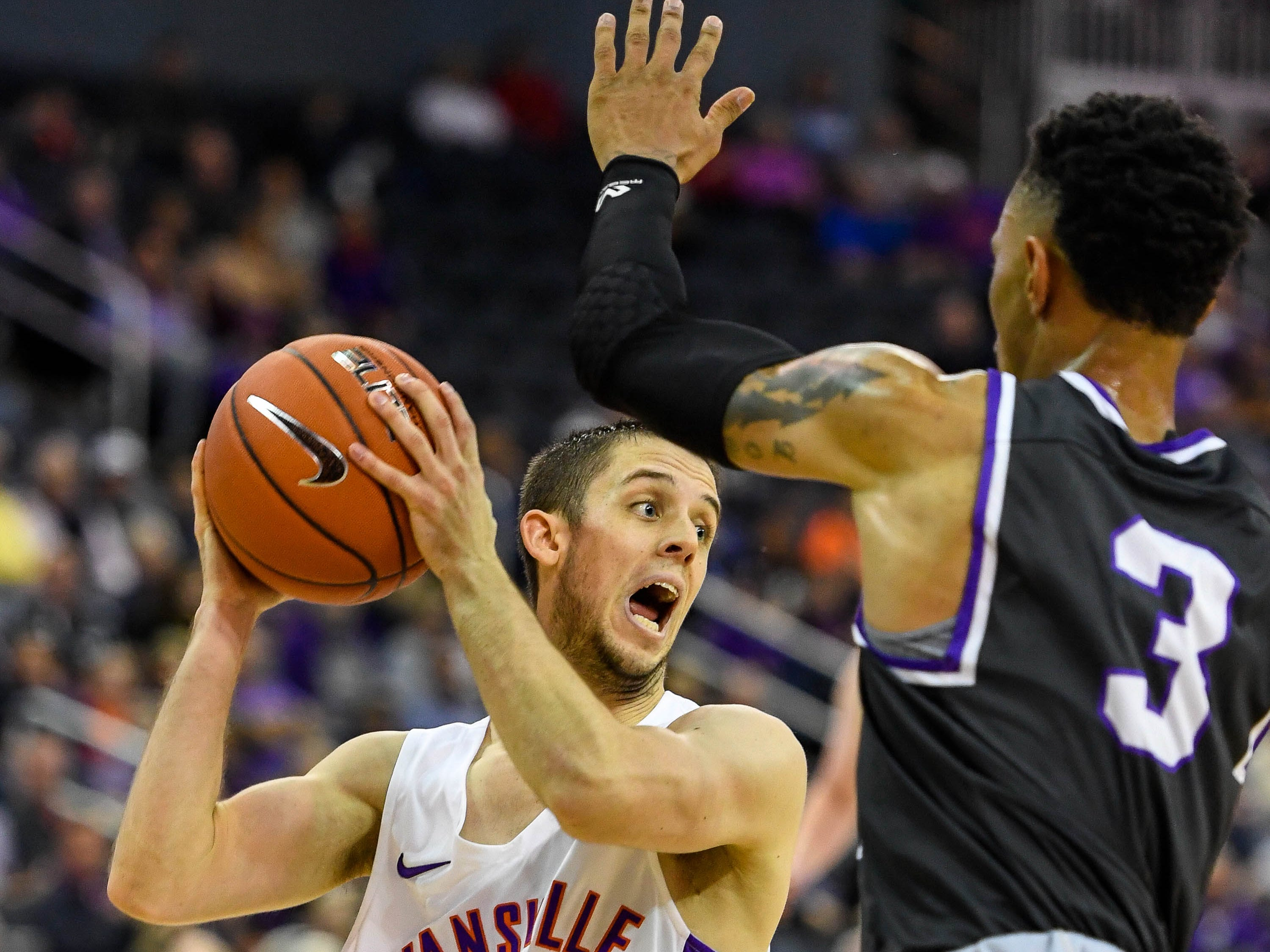 University of Evansville's Shea Feehan (21) looks to pass under pressure from New Mexico Highlands' Gerad Davis(3) as the University of Evansville Purple Aces play the New Mexico Highlands Cowboys in a exhibition game at the Ford Center Saturday, November 3, 2018.
