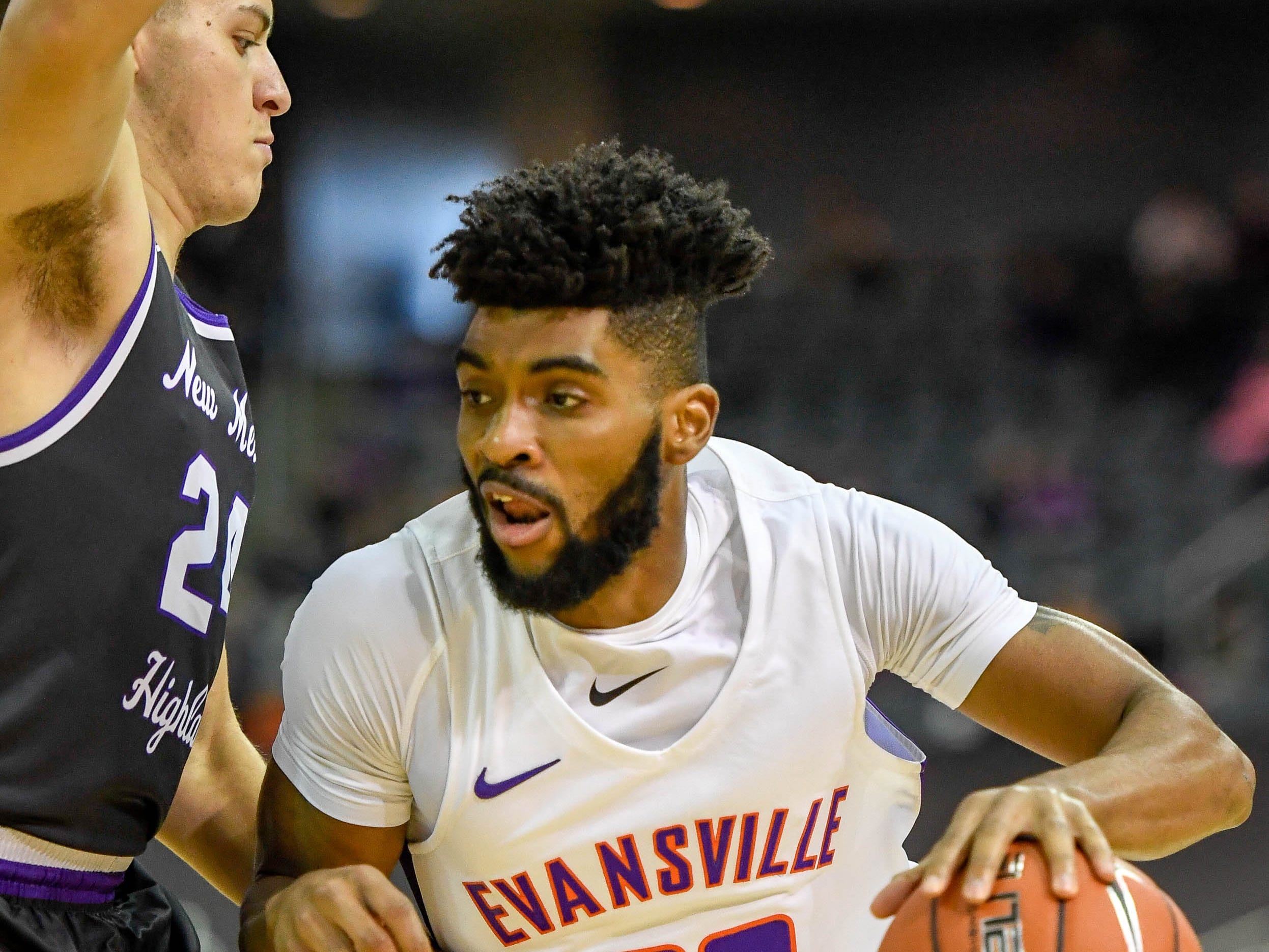 University of Evansville's K.J. Riley (33) drives against defense from New Mexico Highlands' D.J. Bustos (24) as the University of Evansville Purple Aces play the New Mexico Highlands Cowboys in a exhibition game at the Ford Center Saturday, November 3, 2018.