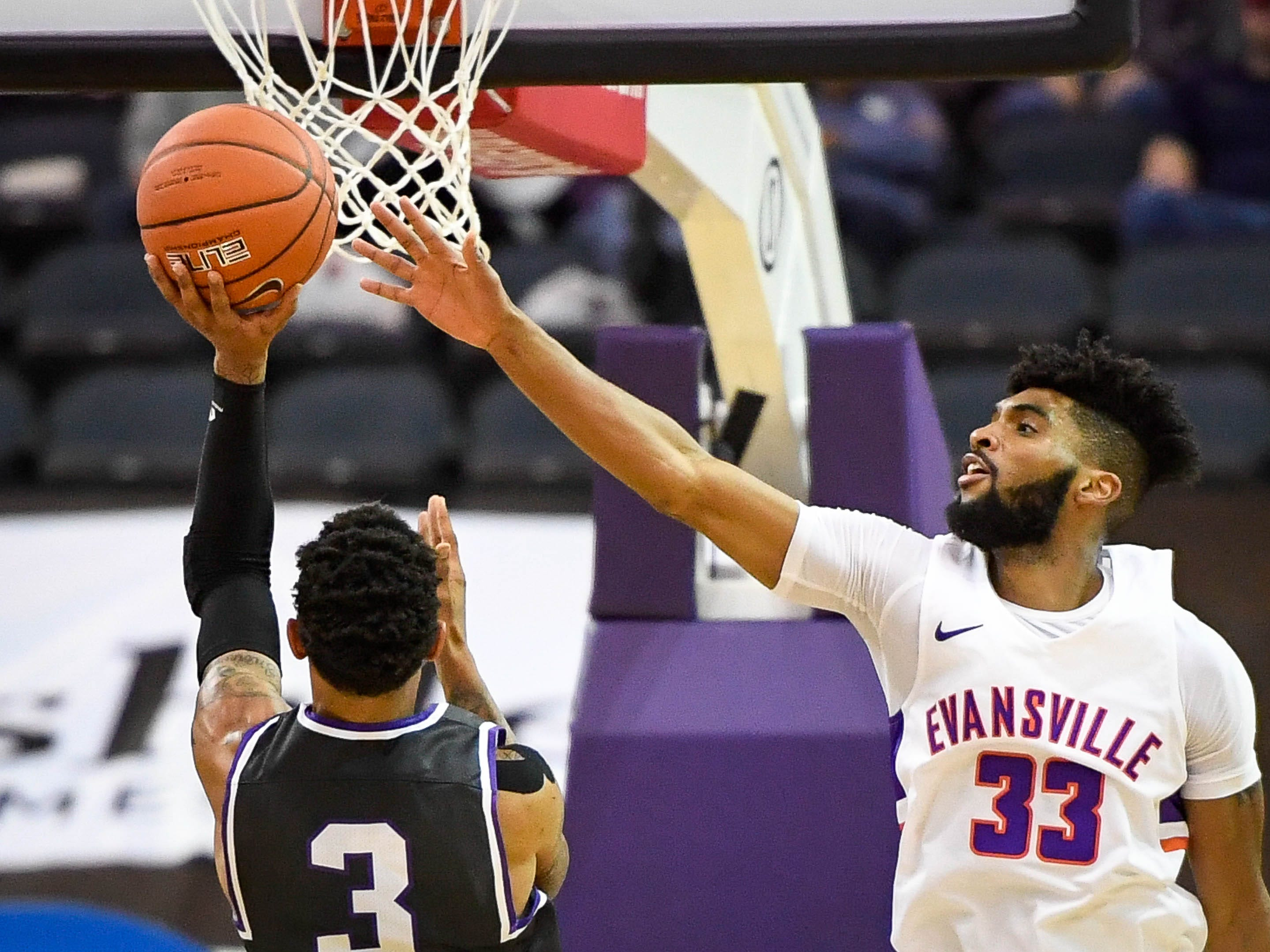 New Mexico Highlands' Gerad Davis (3) shoot against defense from University of Evansville's K.J. Riley (33) as the University of Evansville Purple Aces play the New Mexico Highlands Cowboys in a exhibition game at the Ford Center Saturday, November 3, 2018.