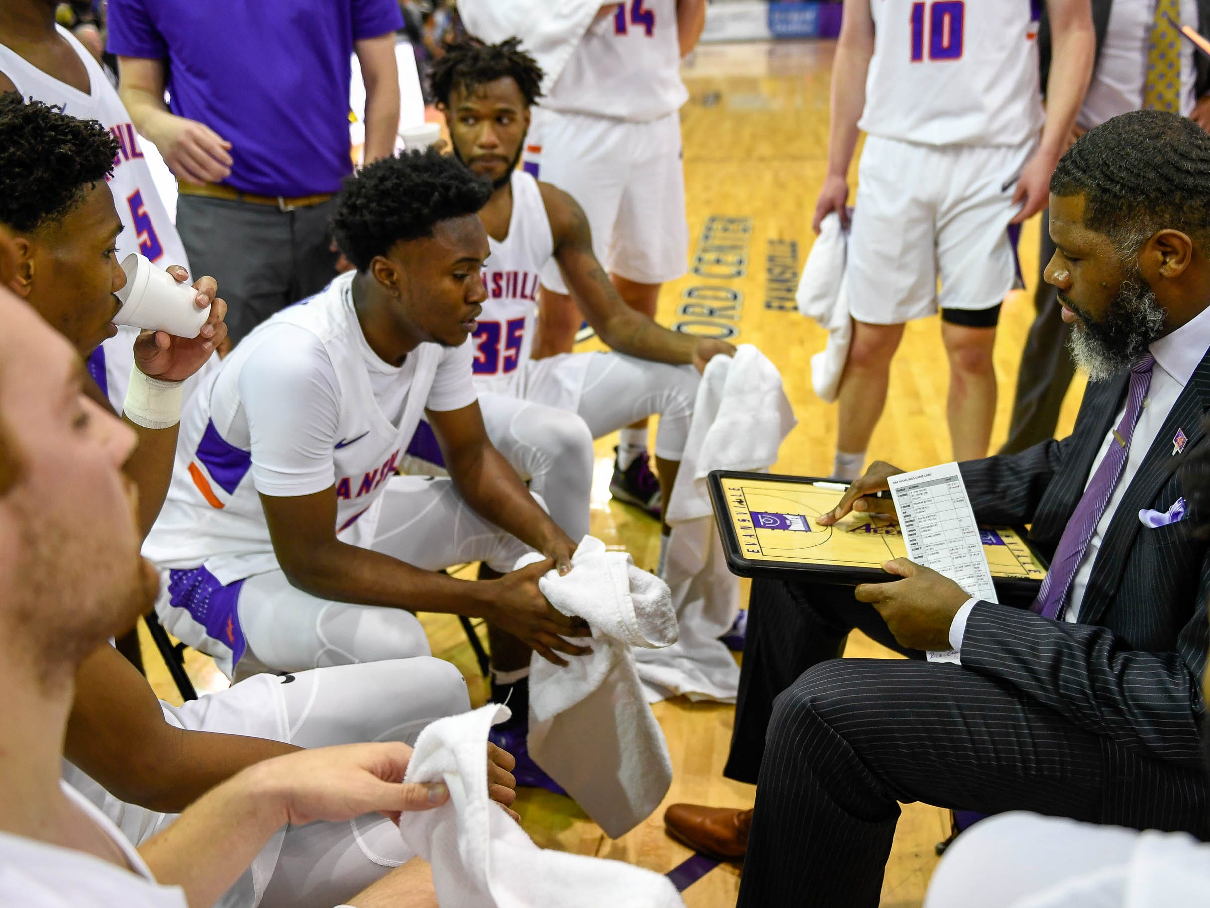 University of Evansville head coach Walter McCarty talks with his team during a timeout as the University of Evansville Purple Aces play the New Mexico Highlands Cowboys in a exhibition game at the Ford Center Saturday, November 3, 2018.