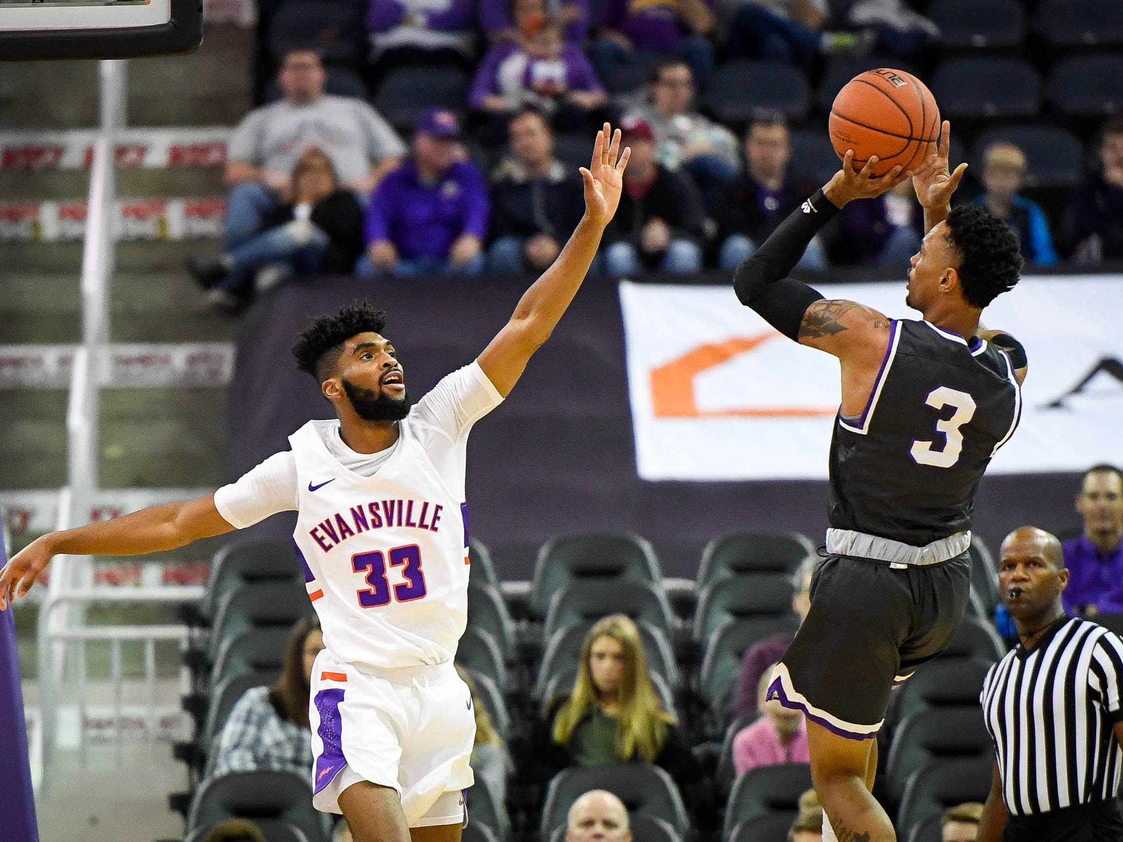 New Mexico Highlands' Gerad Davis(3) shoots over University of Evansville's K.J. Riley (33) as the University of Evansville Purple Aces play the New Mexico Highlands Cowboys in a exhibition game at the Ford Center Saturday, November 3, 2018.