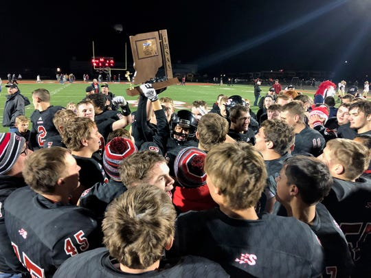 The Southridge Raiders football team celebrates its Class 2A sectional title.
