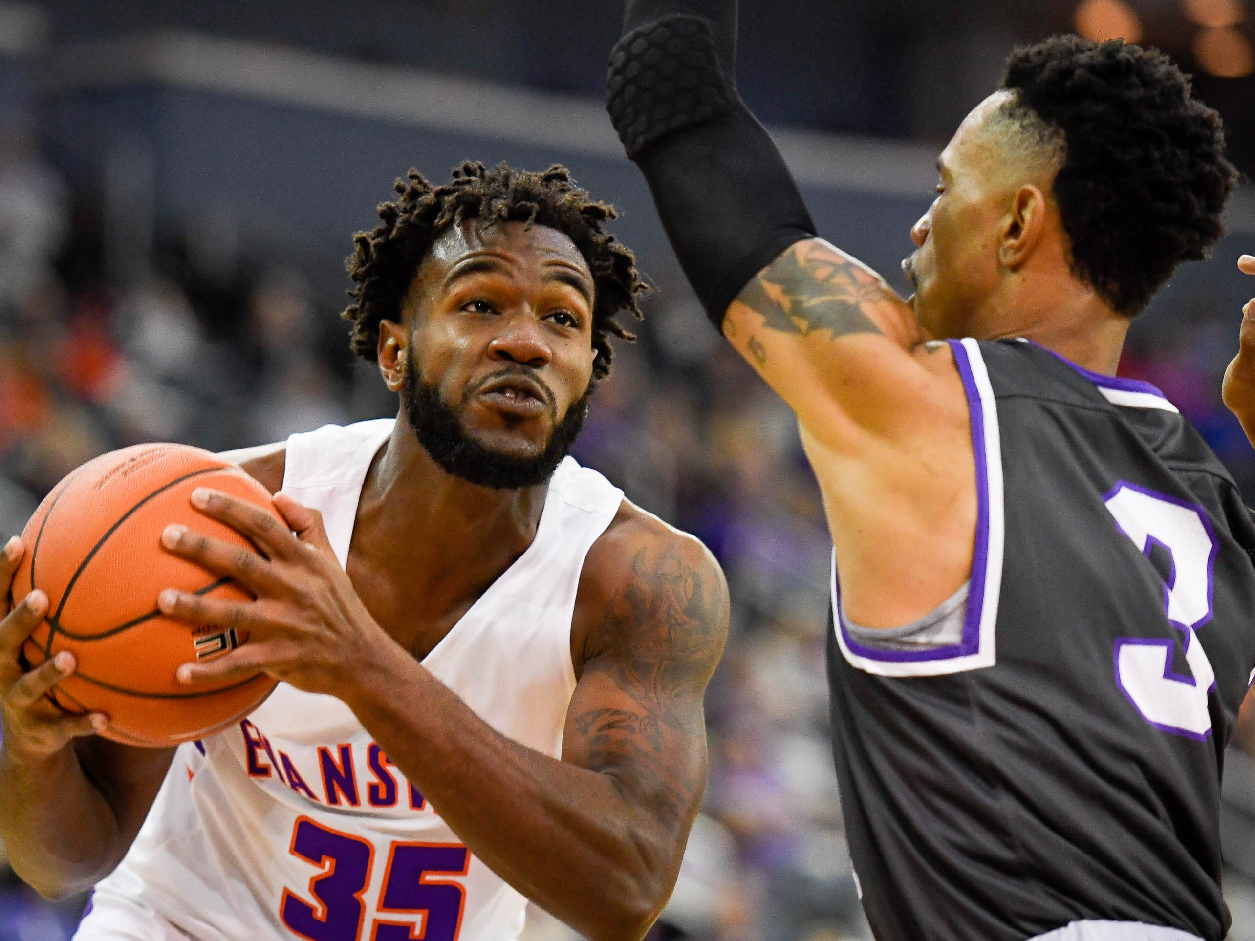University of Evansville's John Hall (35) looks to shoot over New Mexico Highlands' Gerad Davis (3) as the University of Evansville Purple Aces play the New Mexico Highlands Cowboys in a exhibition game at the Ford Center Saturday, November 3, 2018.