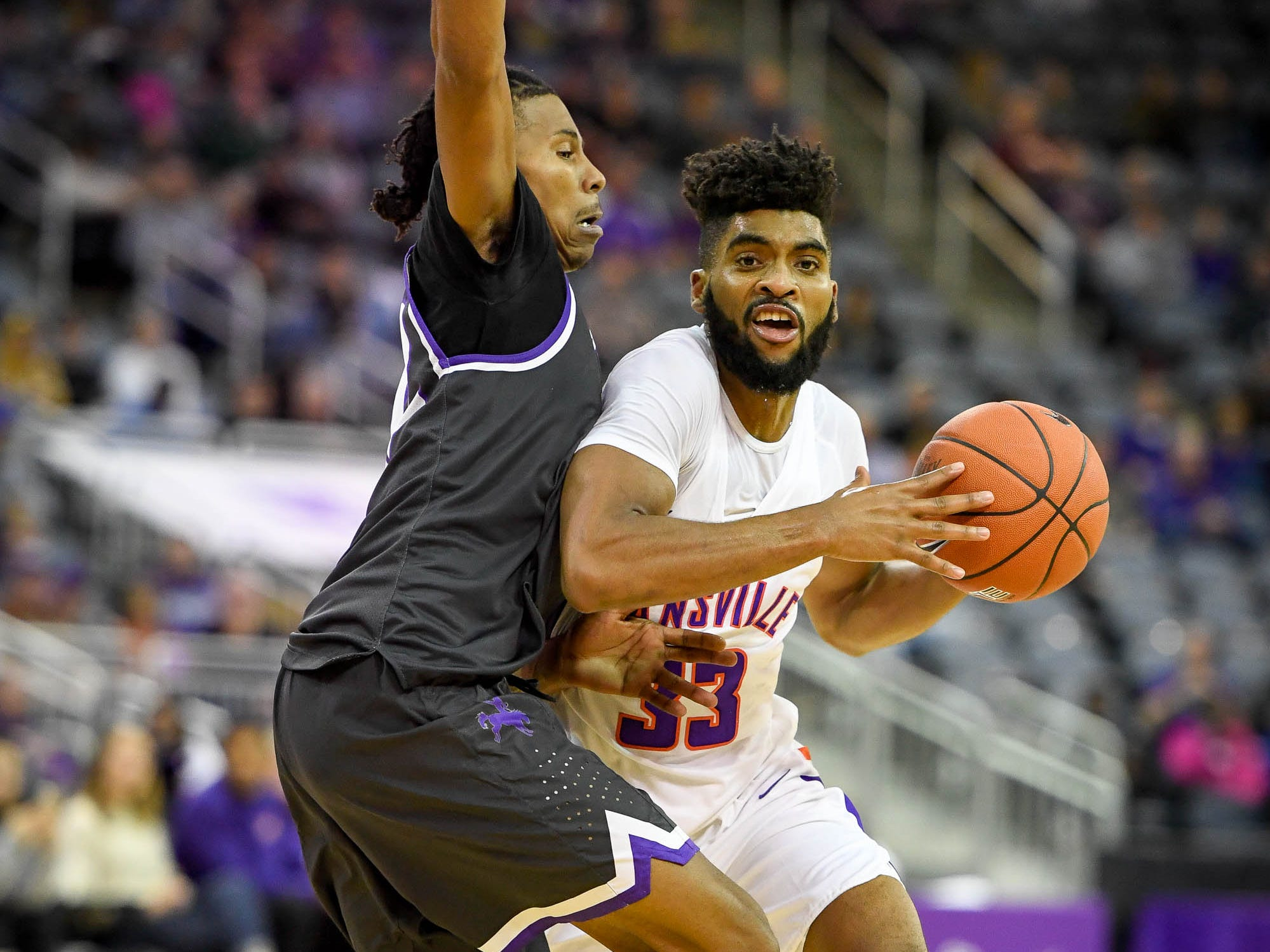 University of Evansville's K.J. Riley (33) drives against New Mexico Highlands' Jeff Collier (22) as the University of Evansville Purple Aces play the New Mexico Highlands Cowboys in a exhibition game at the Ford Center Saturday, November 3, 2018.