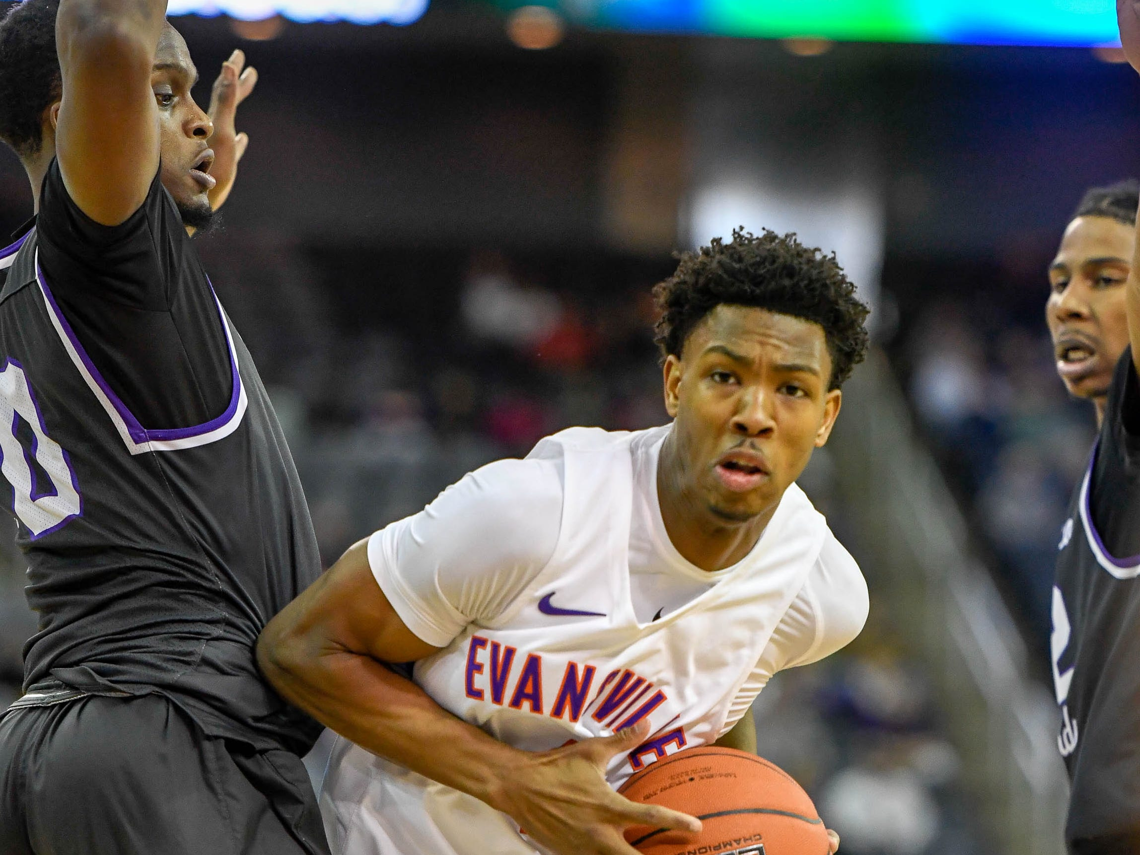 University of Evansville's Marty Hill (1) drives around New Mexico Highlands' Raquan Mitchell (0) as the University of Evansville Purple Aces play the New Mexico Highlands Cowboys in a exhibition game at the Ford Center Saturday, November 3, 2018.