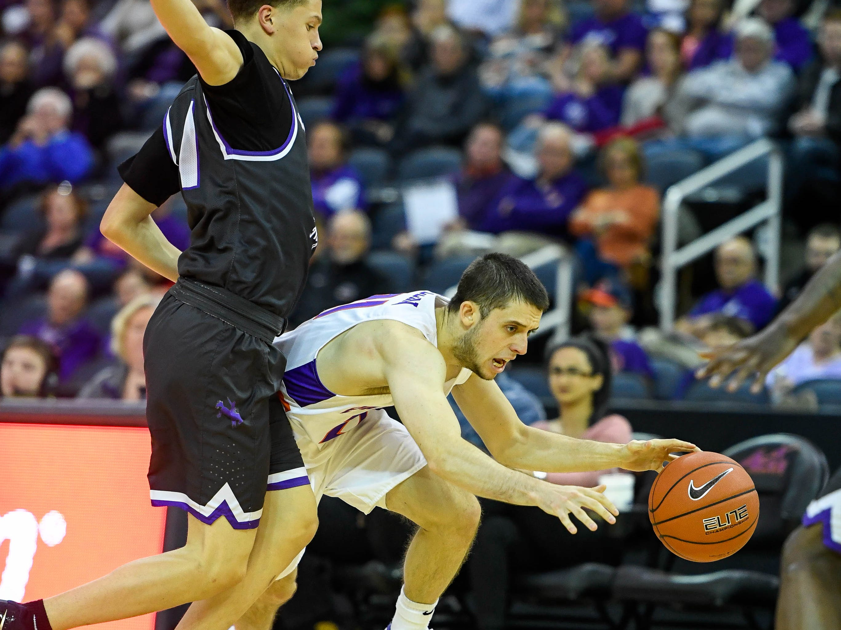 University of Evansville's Shea Feehan (21) drives past New Mexico Highlands' Desmond Carpenter as the University of Evansville Purple Aces play the New Mexico Highlands Cowboys in a exhibition game at the Ford Center Saturday, November 3, 2018.