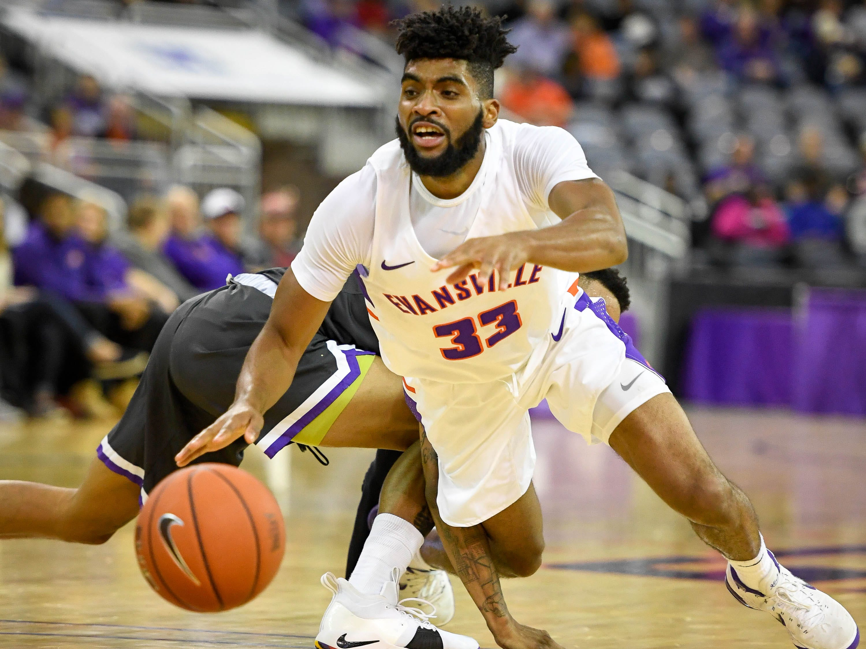 University of Evansville's K.J. Riley (33) gets tangled up with New Mexico Highlands' Gerad Davis (3) as the University of Evansville Purple Aces play the New Mexico Highlands Cowboys in a exhibition game at the Ford Center Saturday, November 3, 2018.