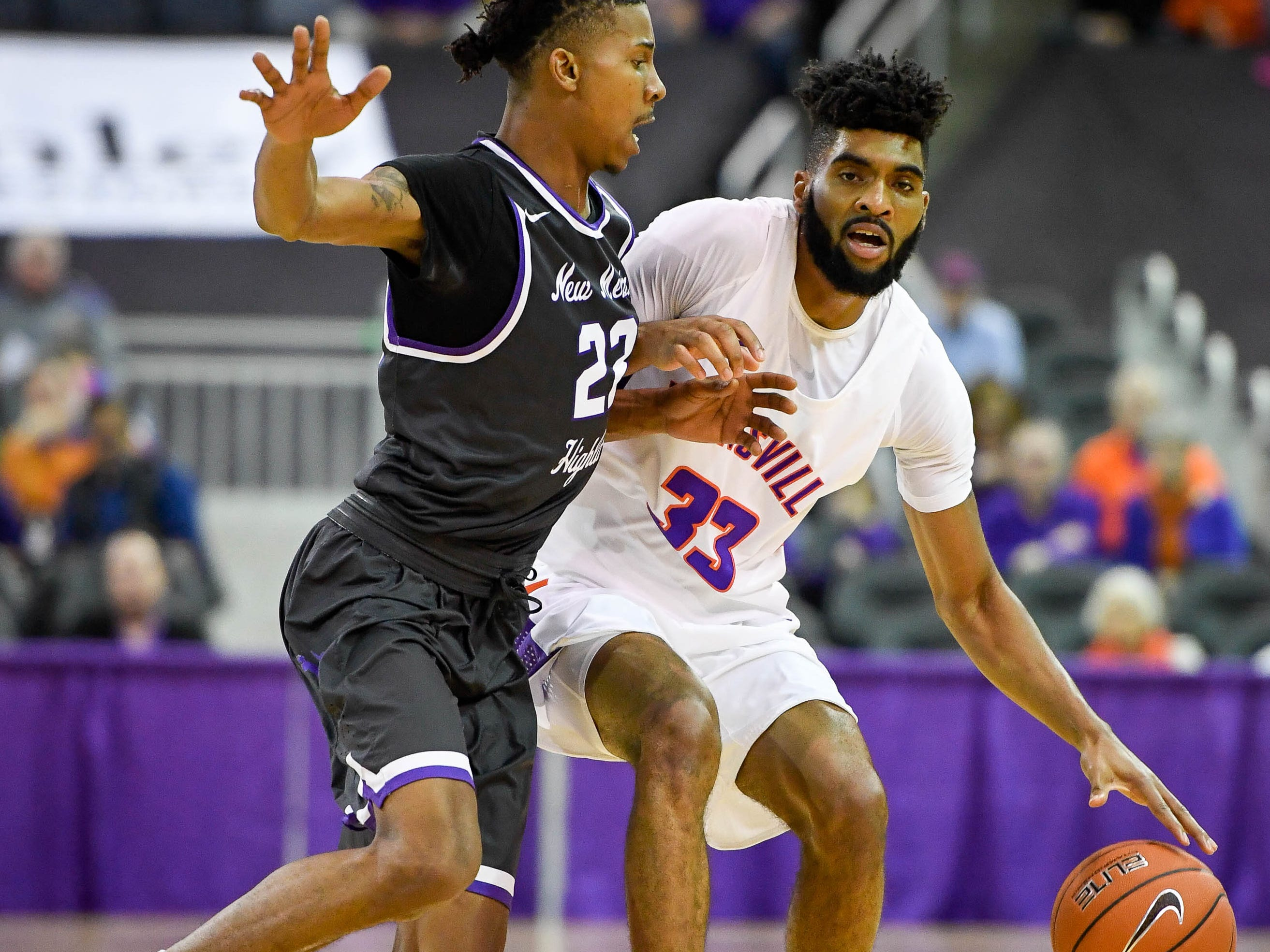 University of Evansville's K.J. Riley (33) drives under pressure from New Mexico Highlands' Marlon Cunningham (23) as the University of Evansville Purple Aces play the New Mexico Highlands Cowboys in a exhibition game at the Ford Center Saturday, November 3, 2018.