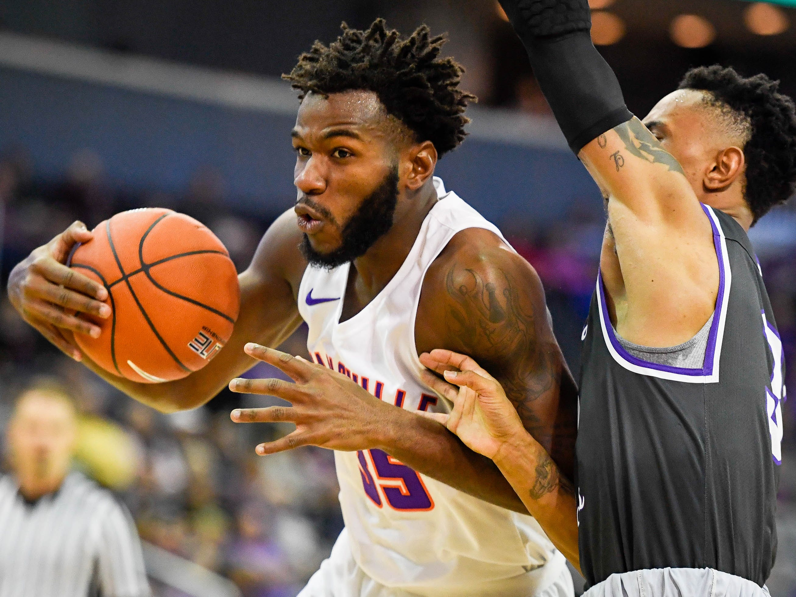 University of Evansville's John Hall (35) drives to the basket against defensive pressure from New Mexico Highlands' Gerad Davis(3) as the University of Evansville Purple Aces play the New Mexico Highlands Cowboys in a exhibition game at the Ford Center Saturday, November 3, 2018.