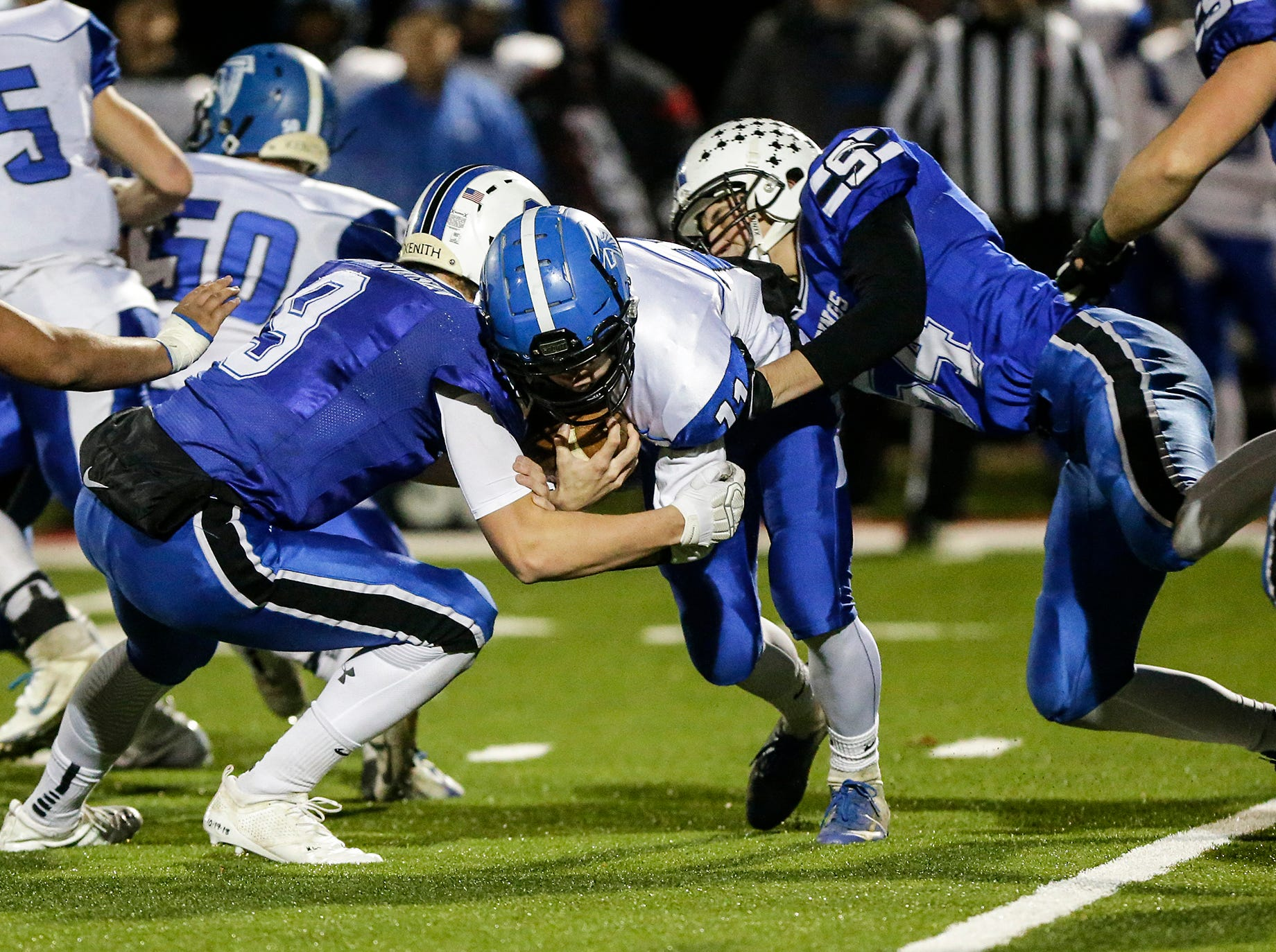 St. Mary's Springs Academy football's Cade Christensen (9) and Jacob Koffman (54) tackle Amherst High School's Lincoln Cullen Friday, November 2, 2018 during their WIAA division 5 level 3 playoff game played in Lomira, Wisconsin. Springs won the game 12-0. Doug Raflik/USA TODAY NETWORK-Wisconsin