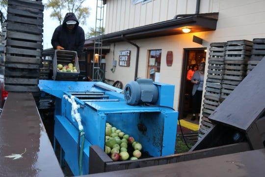 Steve Schmitz, of Schmitz Cider Mill, drops the last bushels of apples into the mill on Saturday.