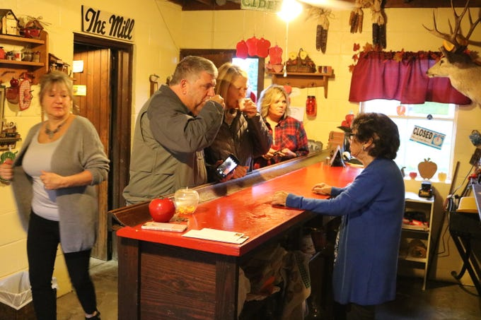 A line of customers taste the last batch of apple cider from Schmitz Cider Mill before buying several gallons on its last day open Saturday.