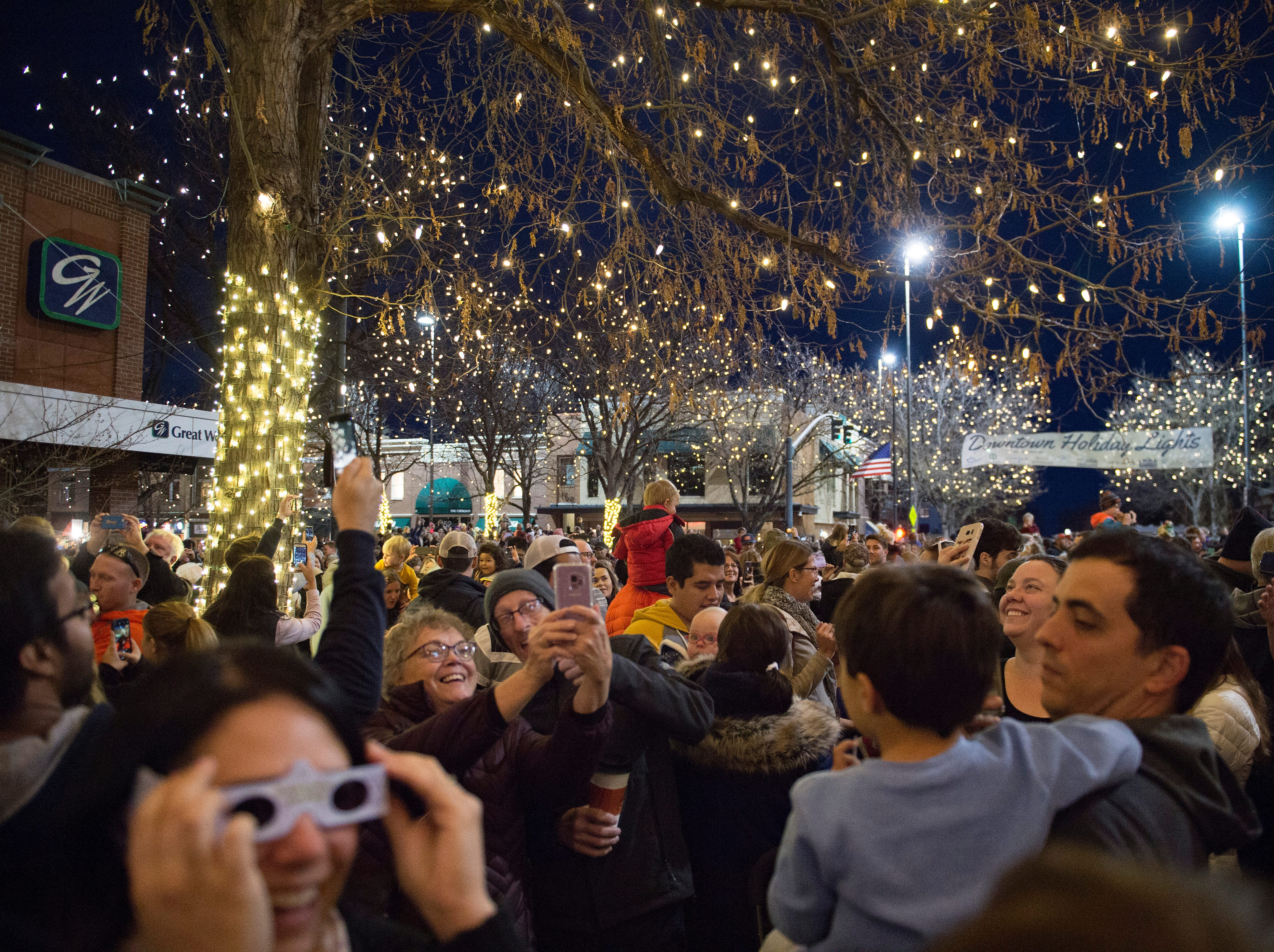 People take photos of the holiday lights in Oak Street Plaza after they turned on in Old Town on Friday, November 2, 2018. The lights will illuminate Old Town until Feb. 14.