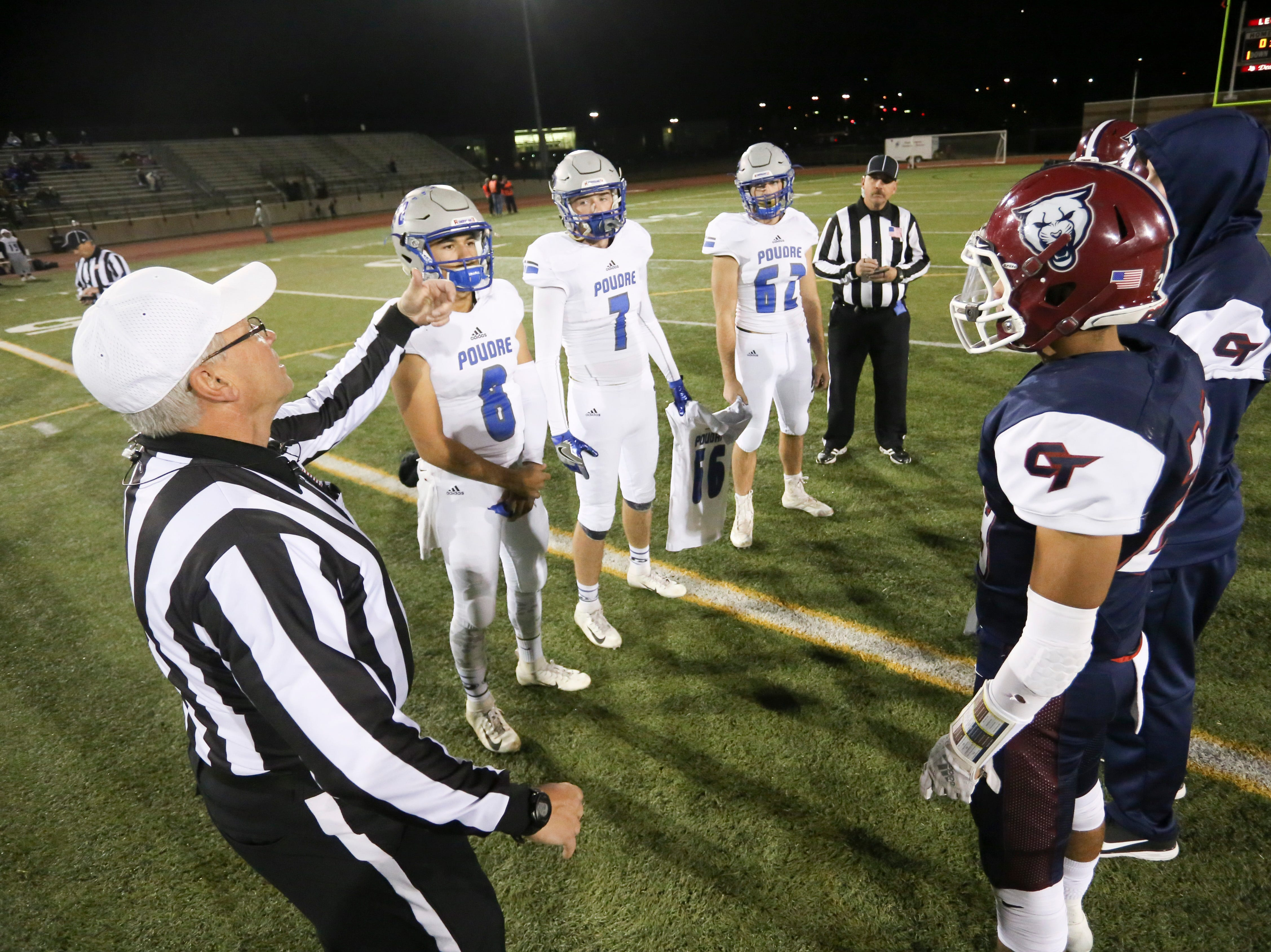 Captains for Poudre High School and Cherokee Trail High School gather for the cointoss before a playoff opening round game on Friday evening in Aurora.