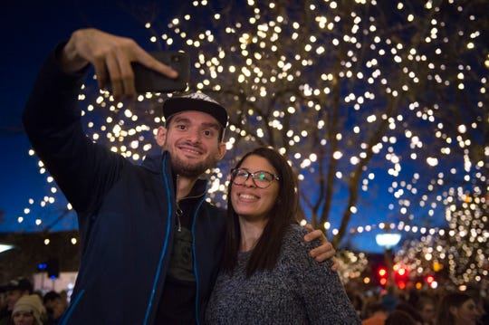 Dejan Markovikj and Jennifer Fermin take a photo after the holiday lights are turned on in Old Town on Friday, November 2, 2018.