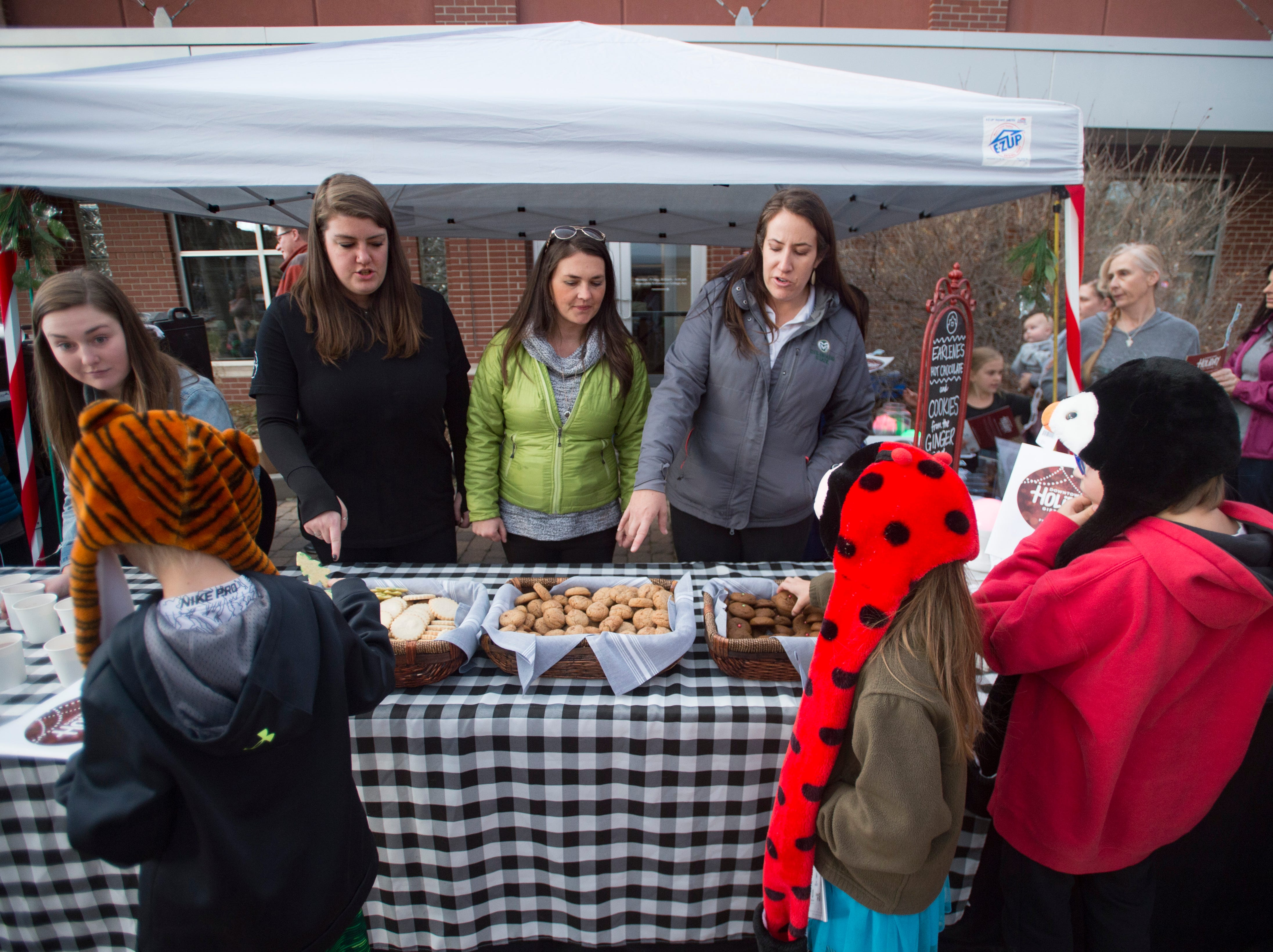 People line up for cookies and hot cocoa in Oak Street Plaza before the holiday lights are turned on in Old Town on Friday, November 2, 2018. College Avenue was closed for public safety during the lighting celebration.